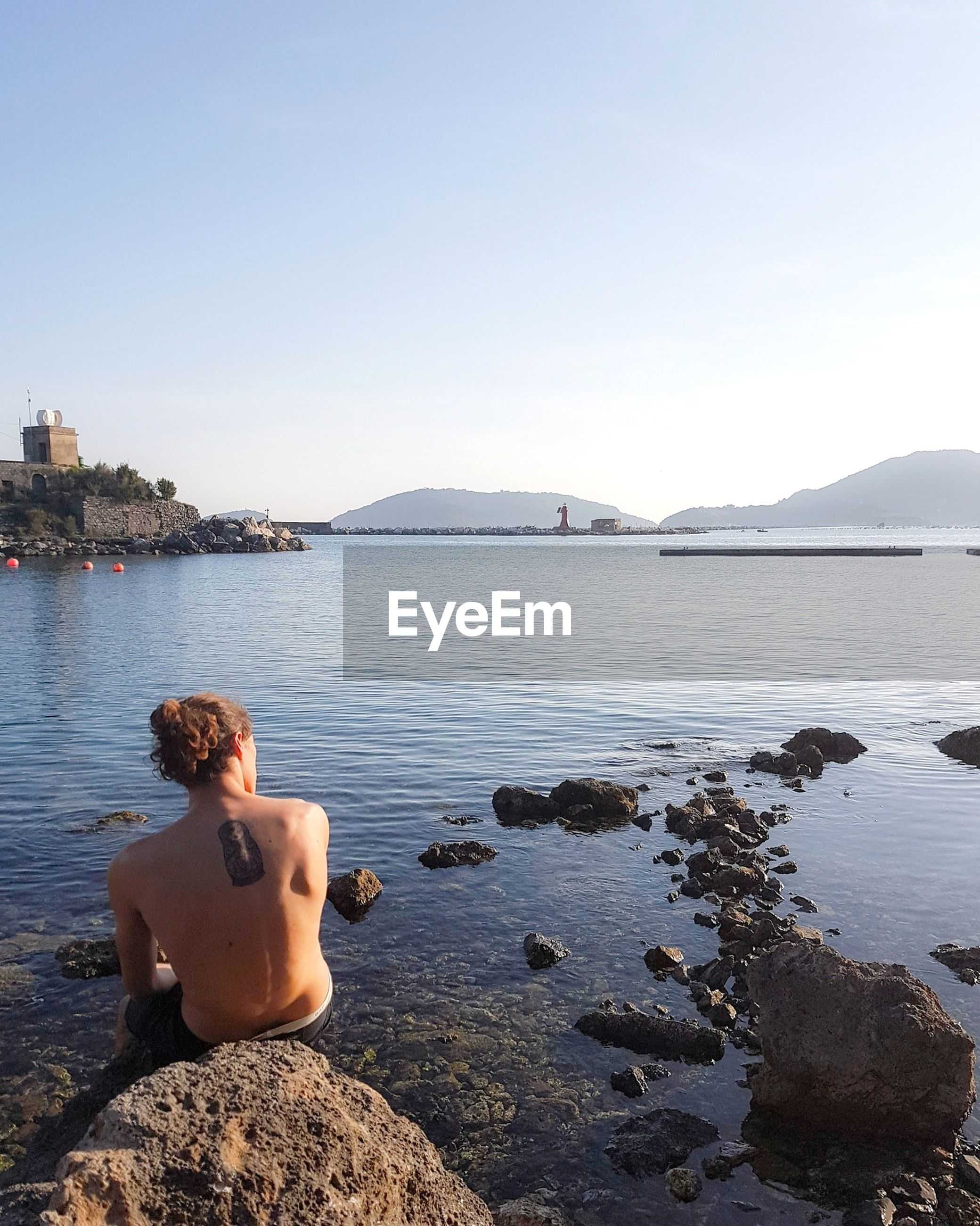 Rear view of shirtless man sitting on rock by lake against sky