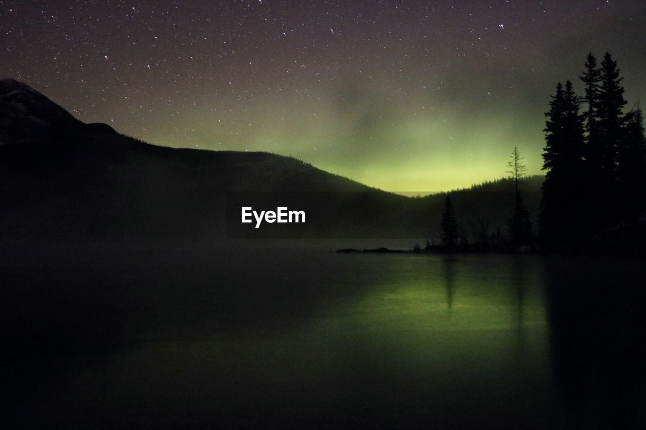 Scenic view of northern lights reflected in lake