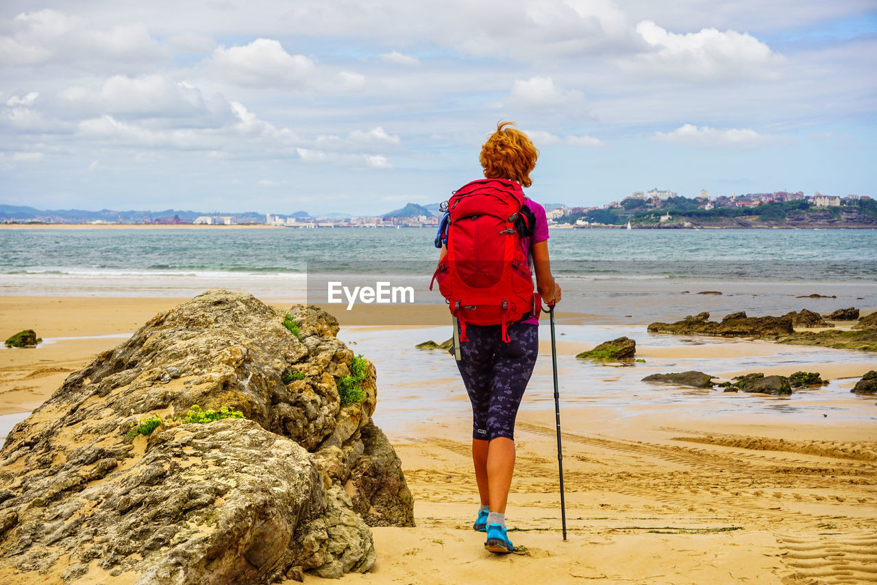 Rear view of woman walking at beach against sky
