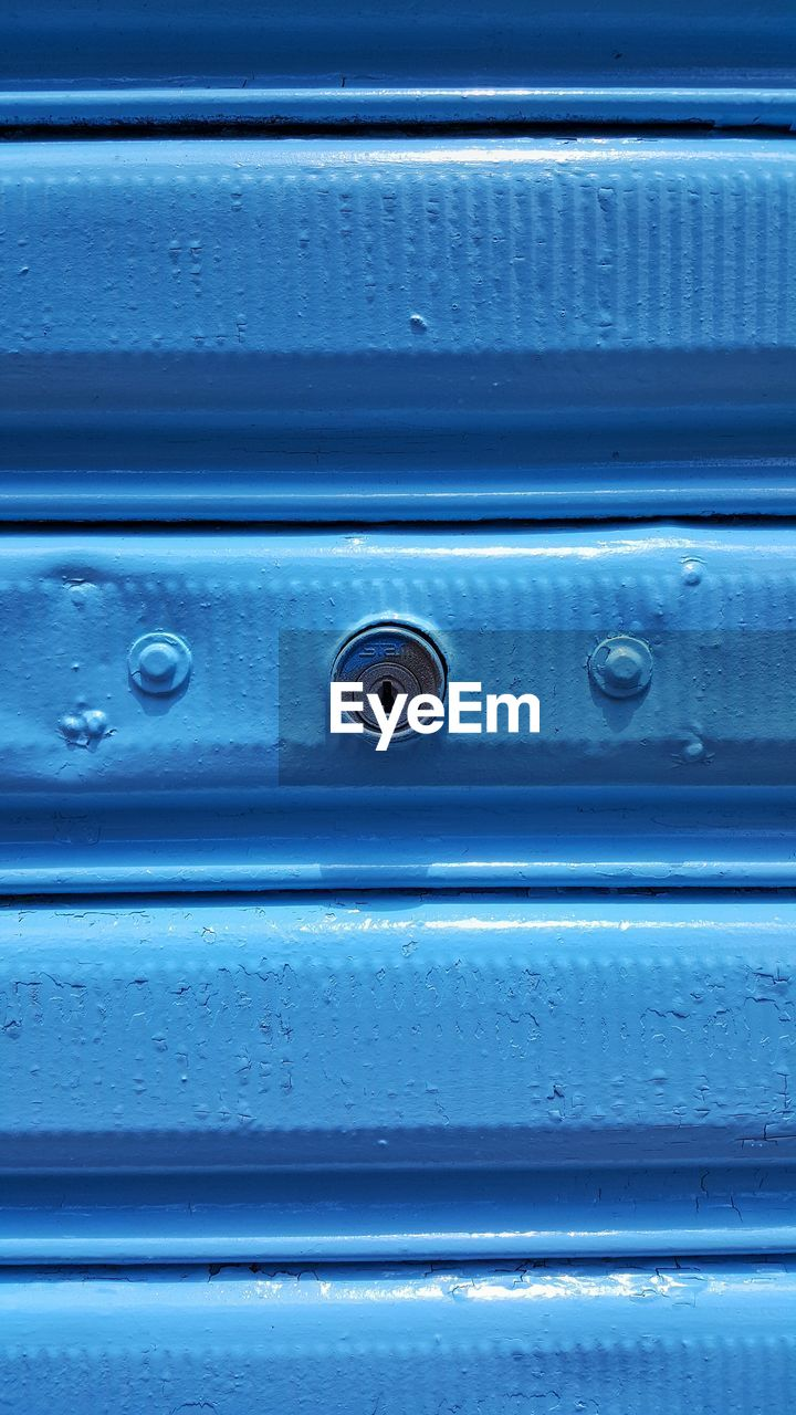 Close-Up Of Keyhole On Blue Metal