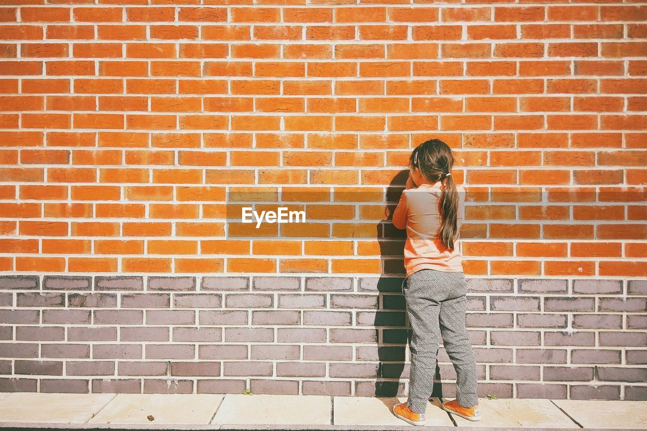 Full length rear view of girl standing by brick wall