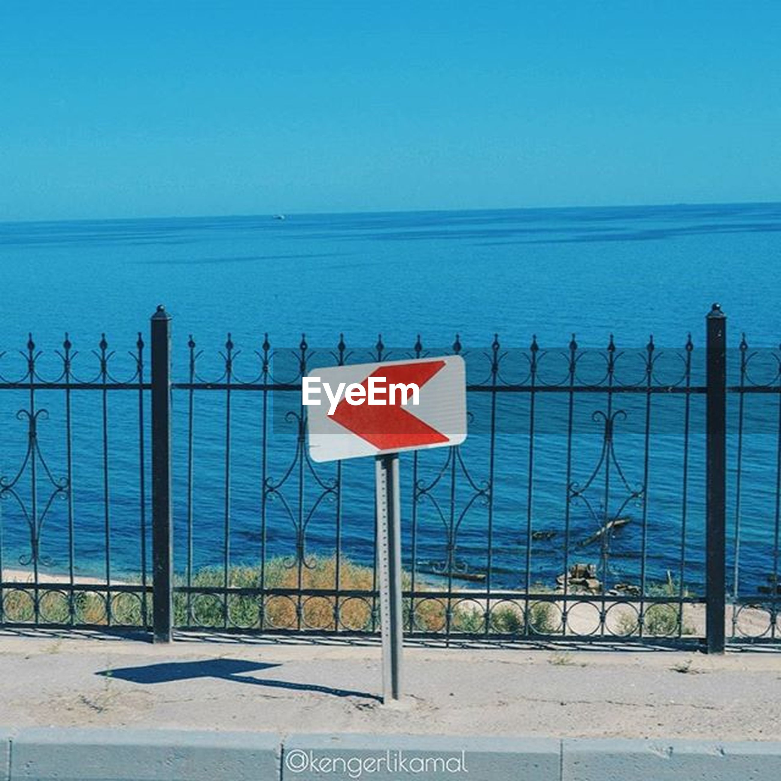 sea, text, western script, water, communication, clear sky, blue, horizon over water, beach, sign, safety, guidance, information sign, warning sign, protection, railing, fence, copy space, security, capital letter
