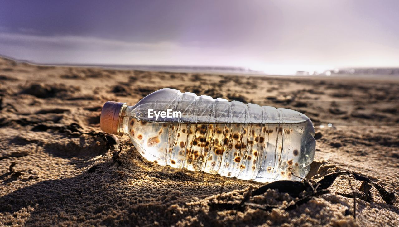 Close-Up Of Water Bottle On Beach Against Sky