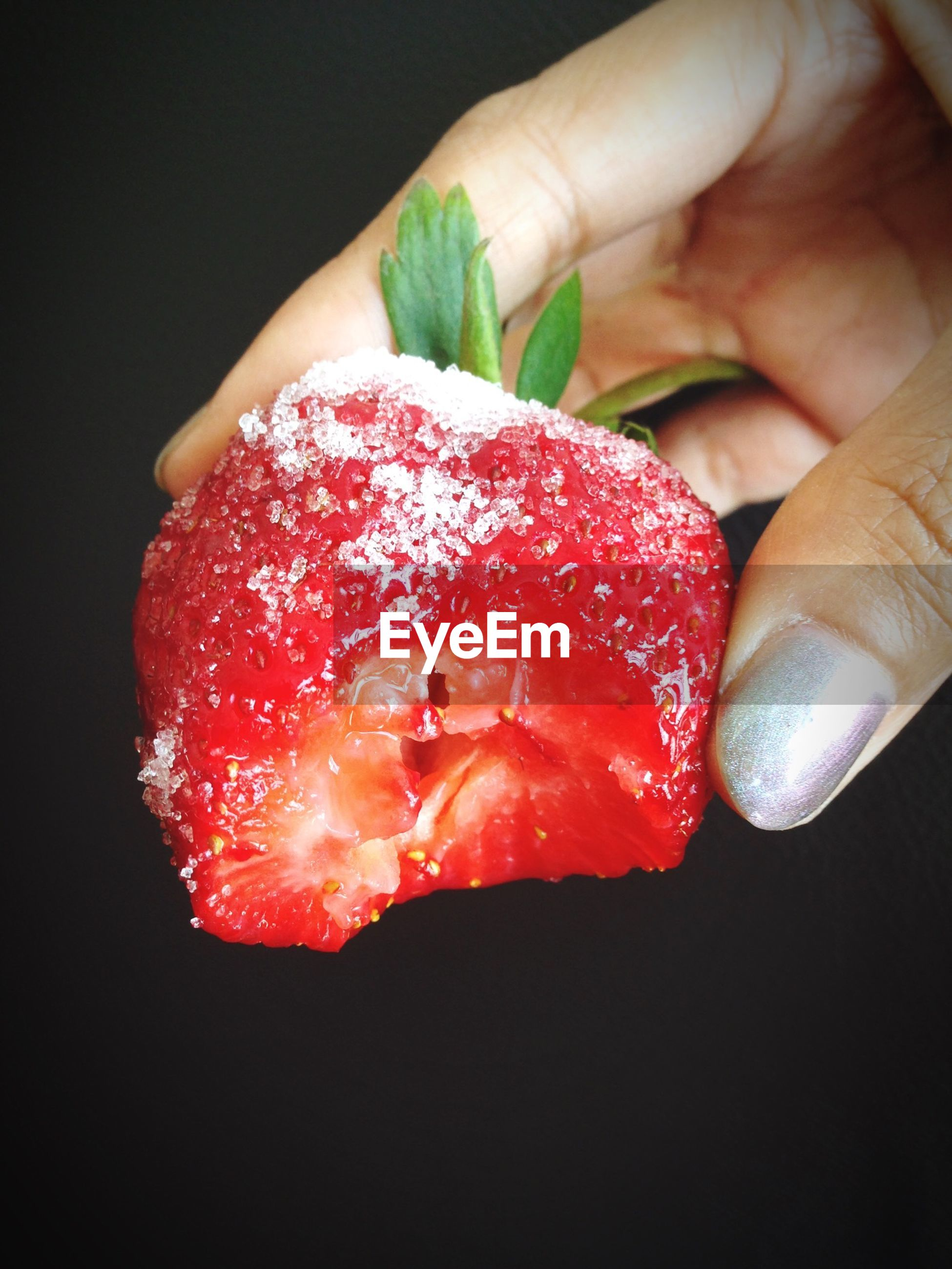 Close-up of woman holding strawberry with bite out of it