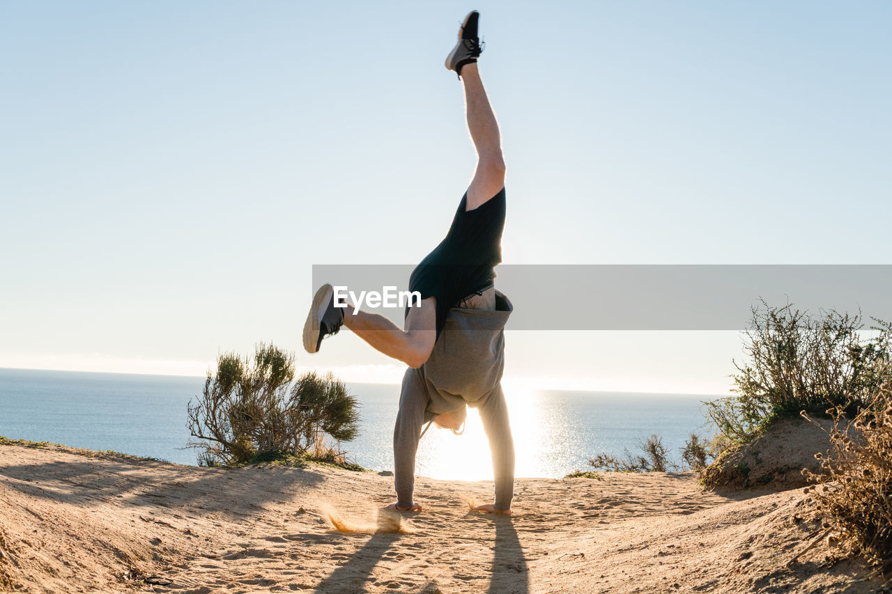 sky, full length, sea, one person, water, lifestyles, land, leisure activity, nature, sunlight, real people, vitality, beauty in nature, beach, day, clear sky, scenics - nature, sport, handstand, outdoors, arms raised, human arm, horizon over water