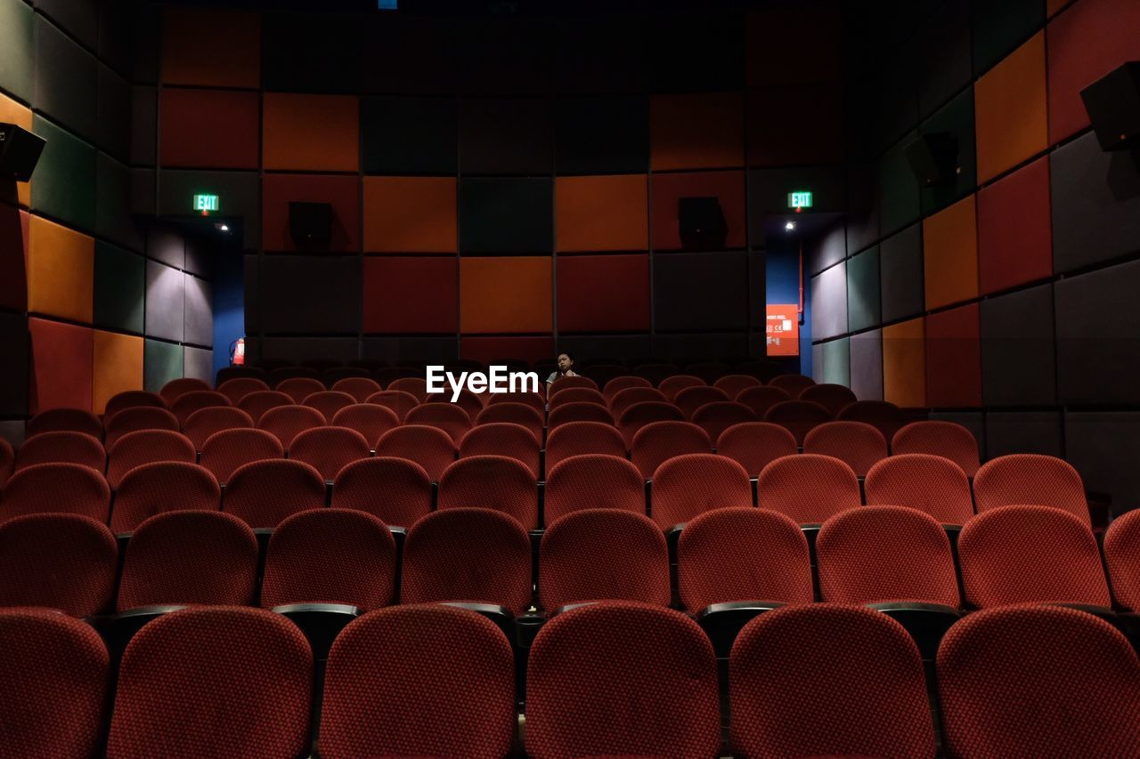seat, in a row, arts culture and entertainment, chair, movie theater, indoors, empty, illuminated, red, absence, no people, film industry, auditorium, side by side, repetition, pattern, large group of objects, stage theater, light, arrangement, ceiling