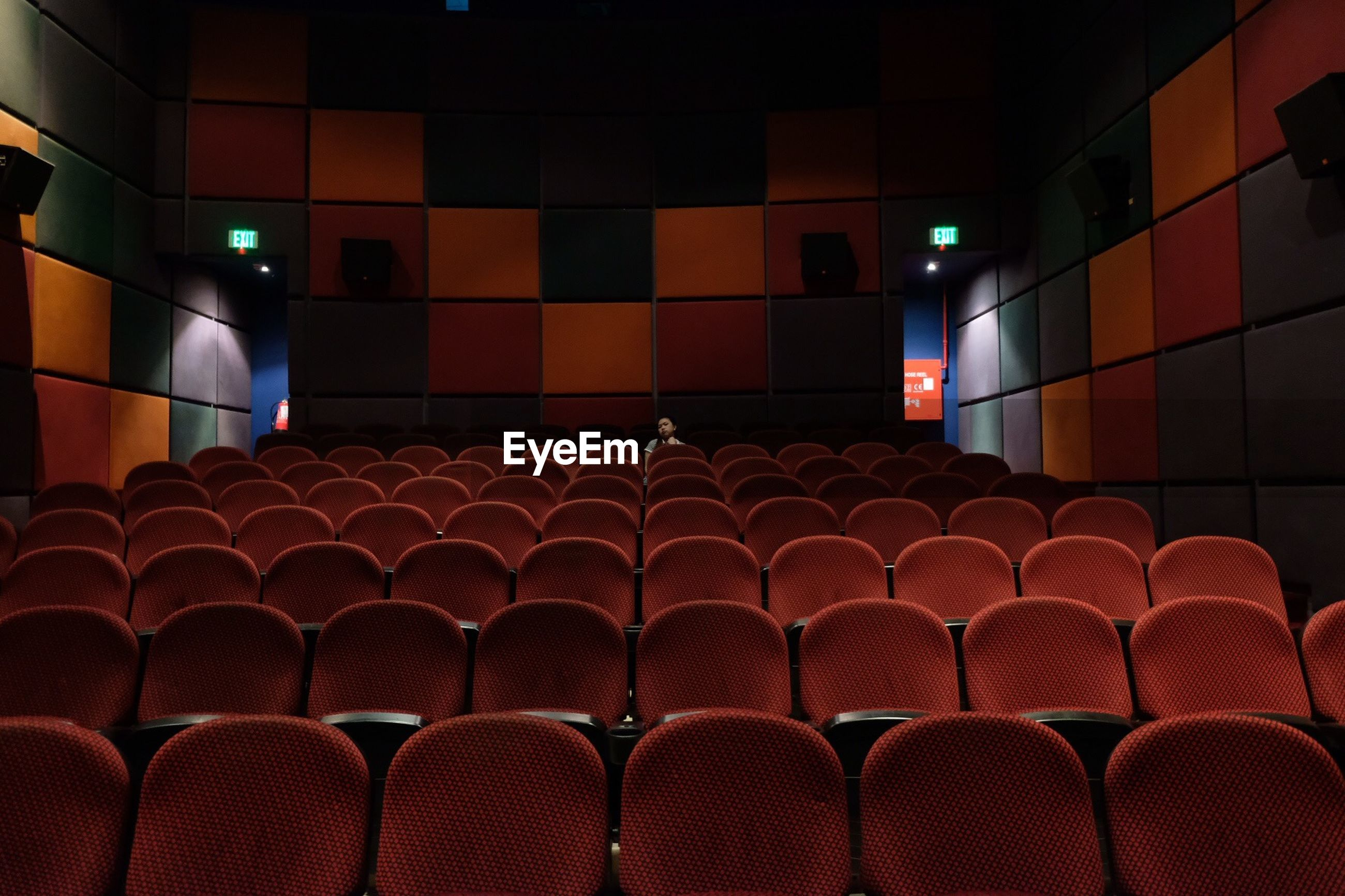 Woman sitting on chair in movie theater