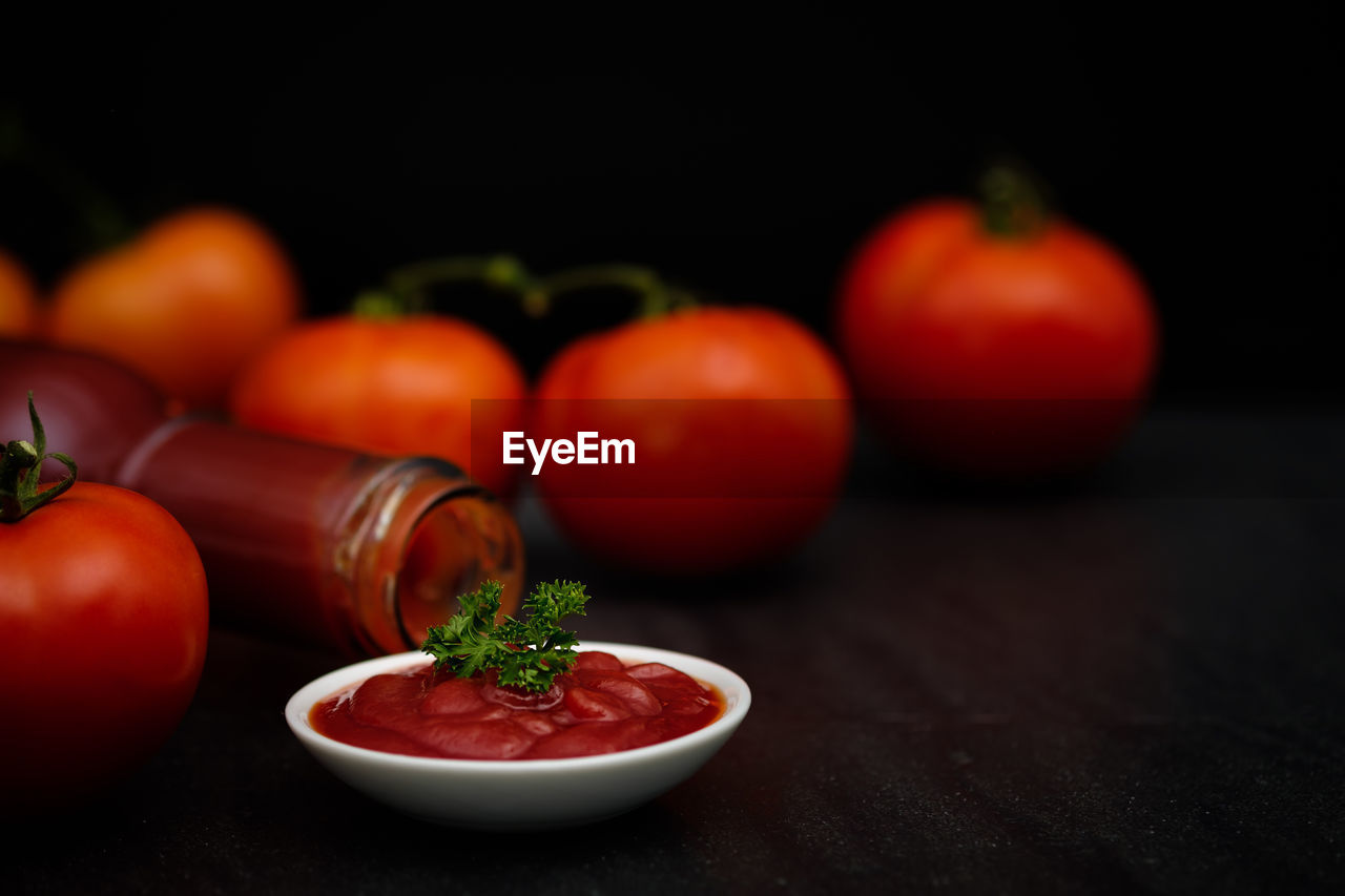 Close-up of tomatoes and ketchup on table