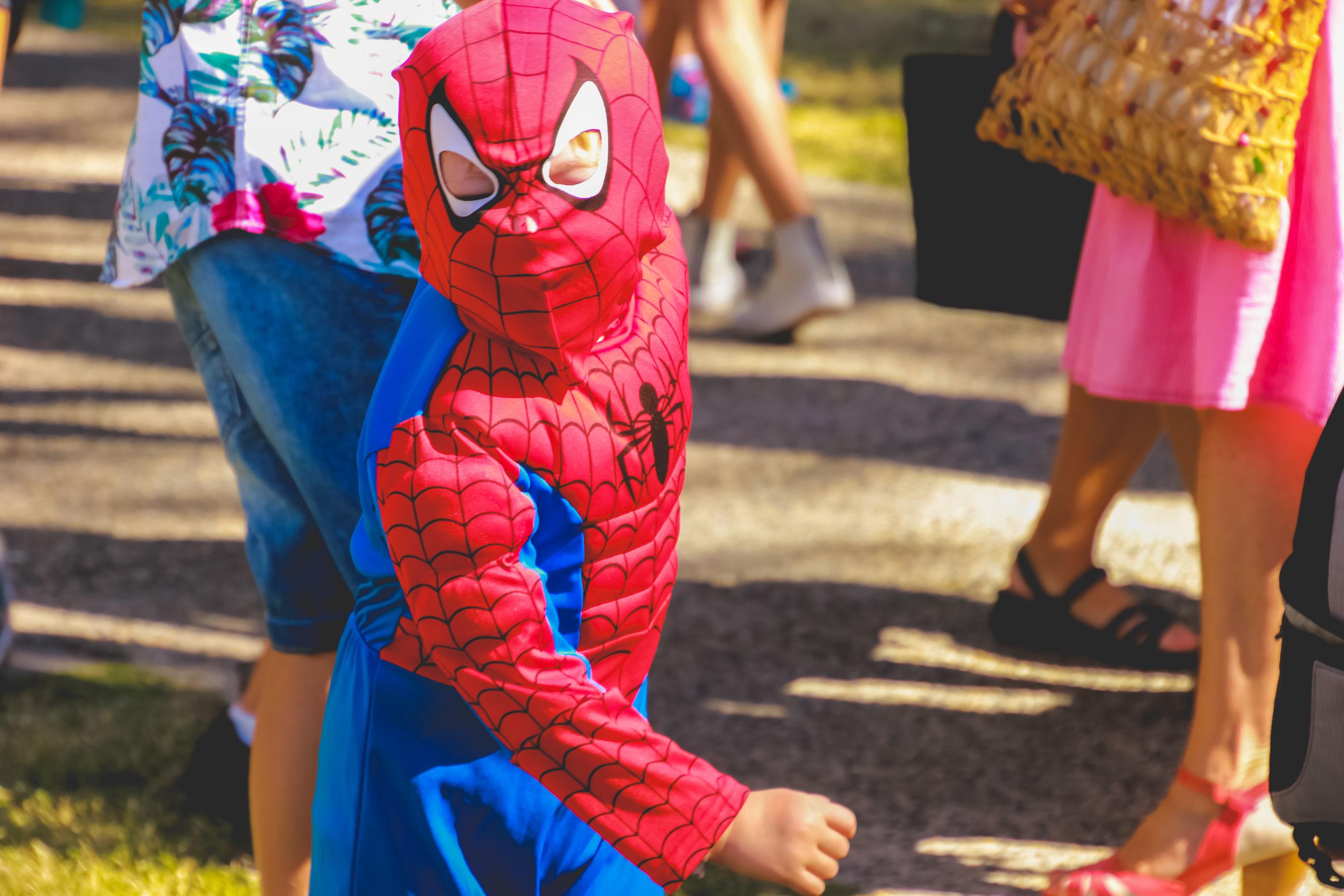 Child wearing superhero costume on street