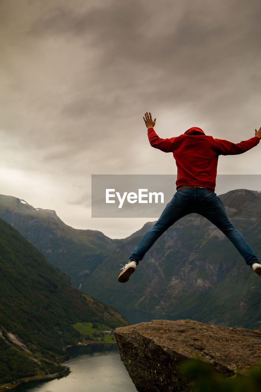 mountain, sky, one person, full length, cloud - sky, jumping, scenics - nature, beauty in nature, leisure activity, nature, mountain range, mid-air, day, real people, human arm, limb, lifestyles, tranquility, casual clothing, freedom, outdoors, arms raised