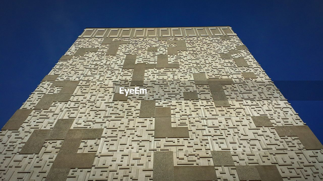 low angle view, clear sky, text, architecture, no people, pattern, sunlight, day, built structure, outdoors, skyscraper, building exterior, sky, close-up