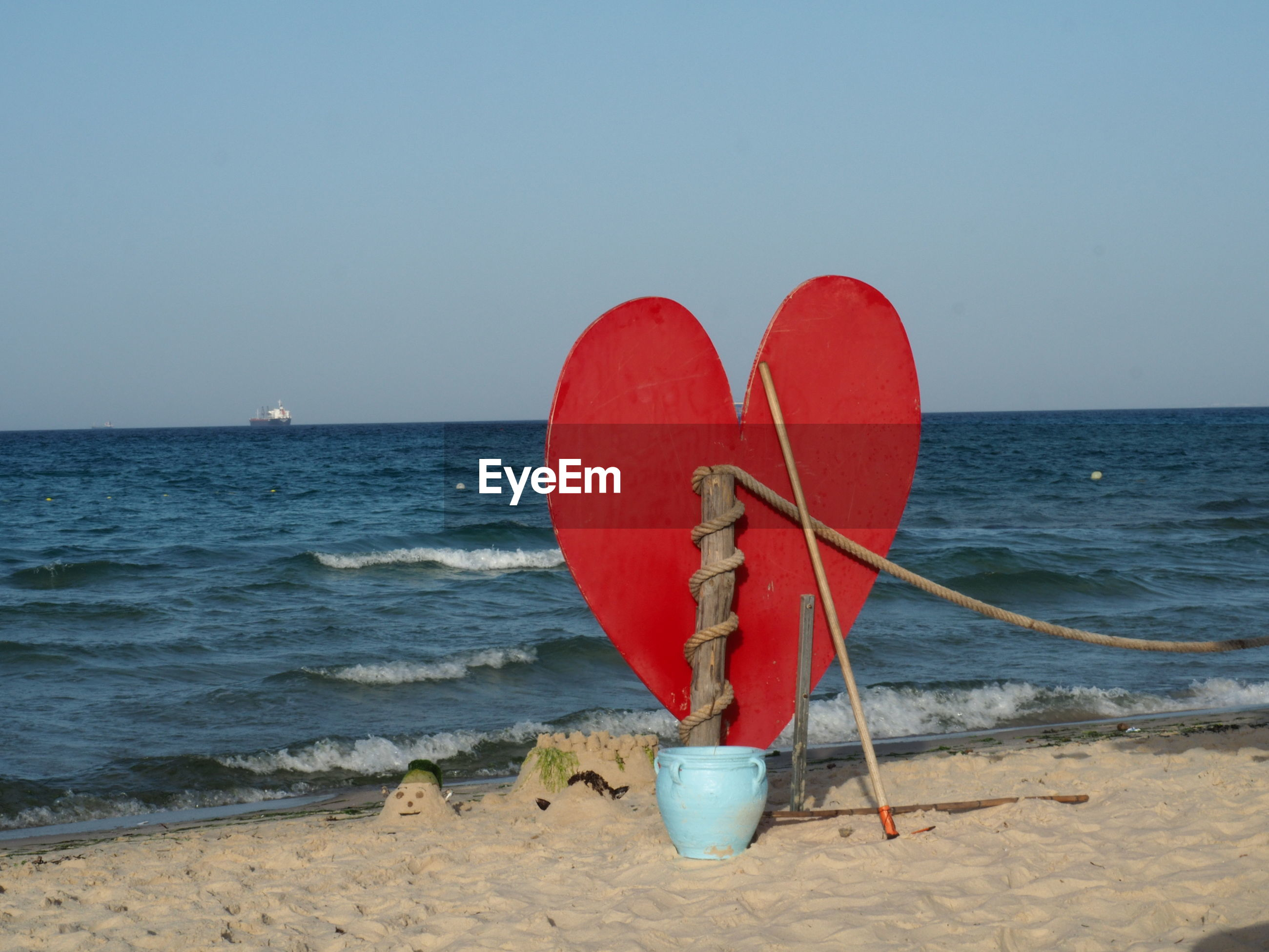 RED HEART SHAPE OVER BEACH AGAINST SKY