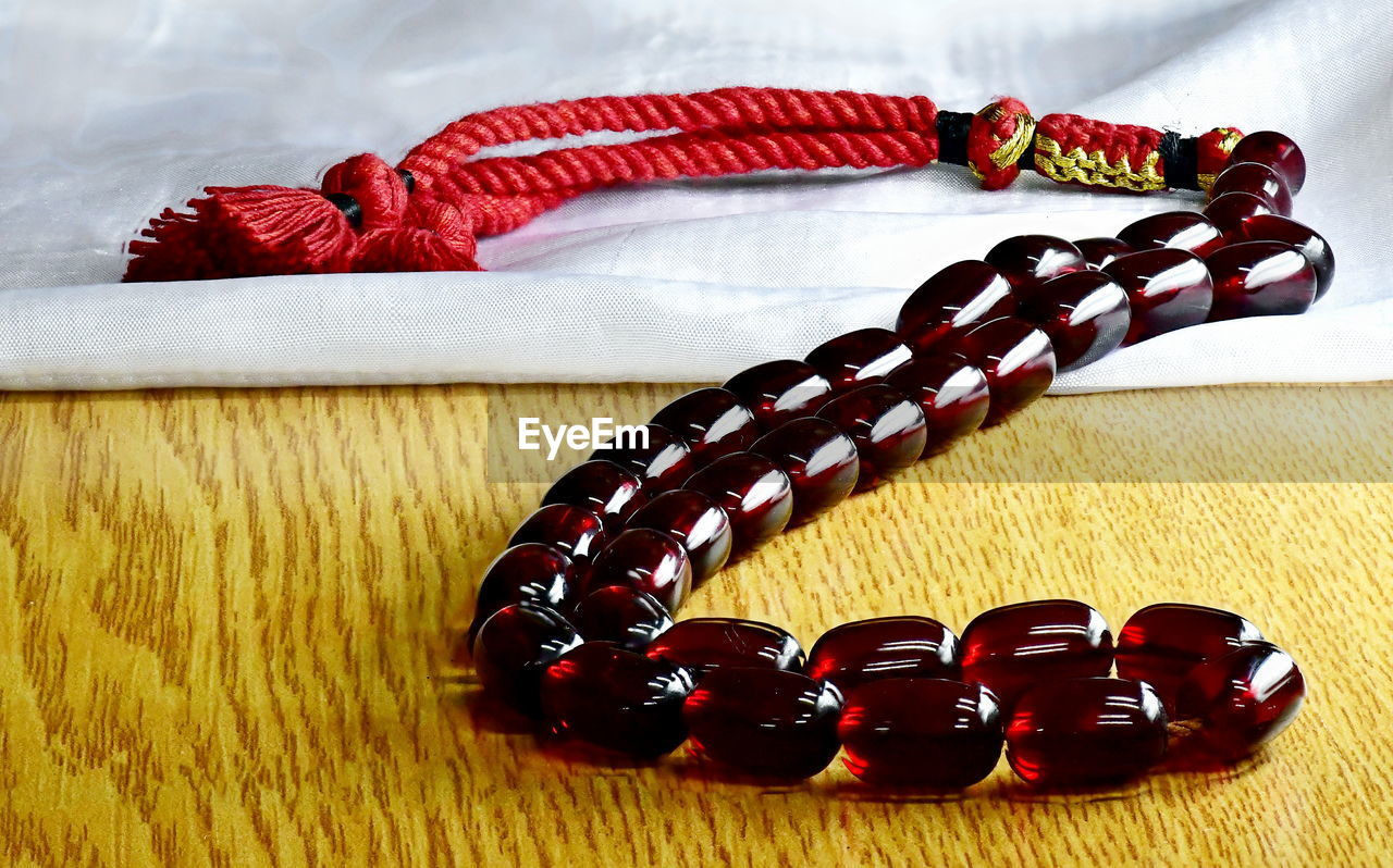 still life, table, indoors, no people, close-up, bead, bracelet, jewelry, necklace, focus on foreground, red, personal accessory, fashion, wood - material, multi colored, high angle view, textile, variation, choice, ornament, temptation