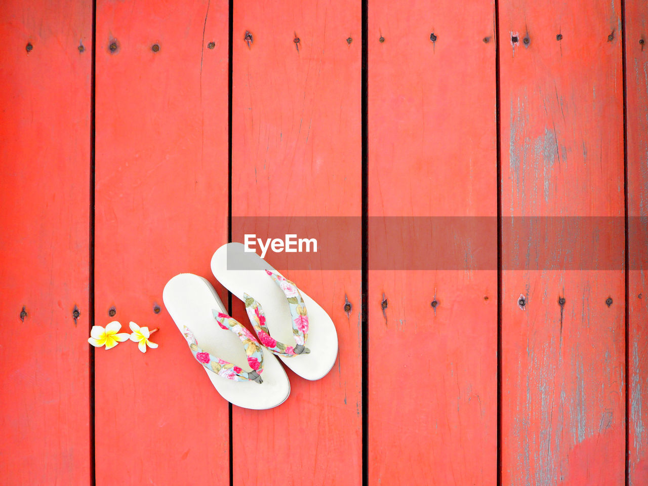 Directly Above Shot Of Flowers And Slippers On Red Floorboard