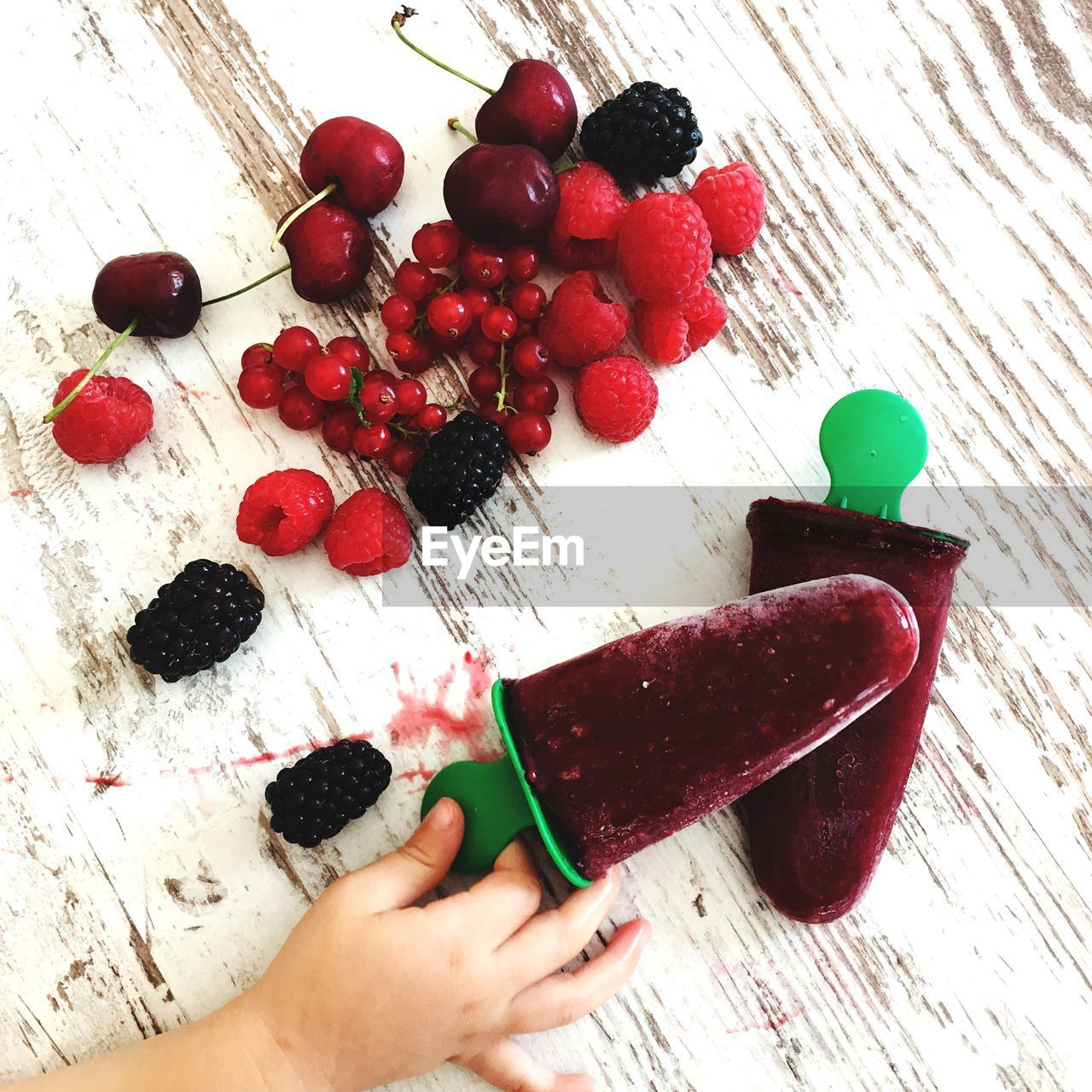 human hand, food, berry fruit, food and drink, fruit, hand, red, healthy eating, table, high angle view, human body part, indoors, freshness, real people, human finger, finger, one person, wood - material, wellbeing, body part, temptation, nail