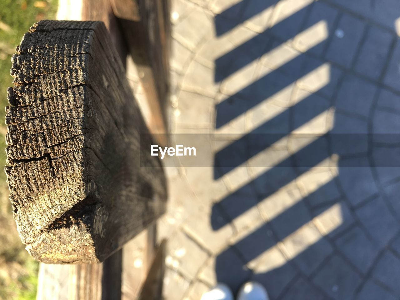 Directly above view of wooden fence with shadow on footpath