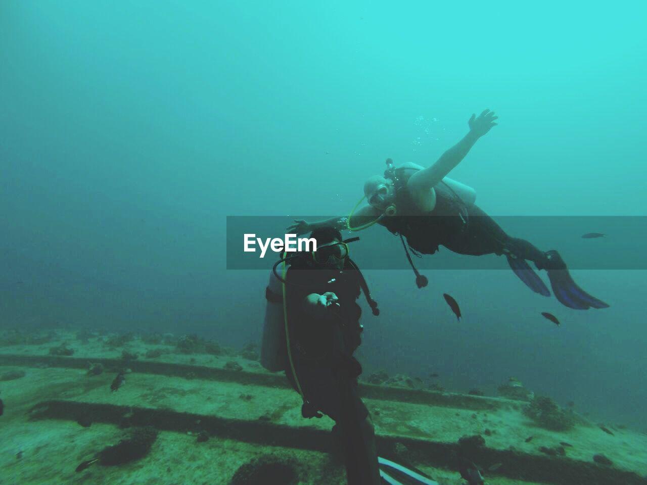 Scuba Drivers Swimming In Blue Sea
