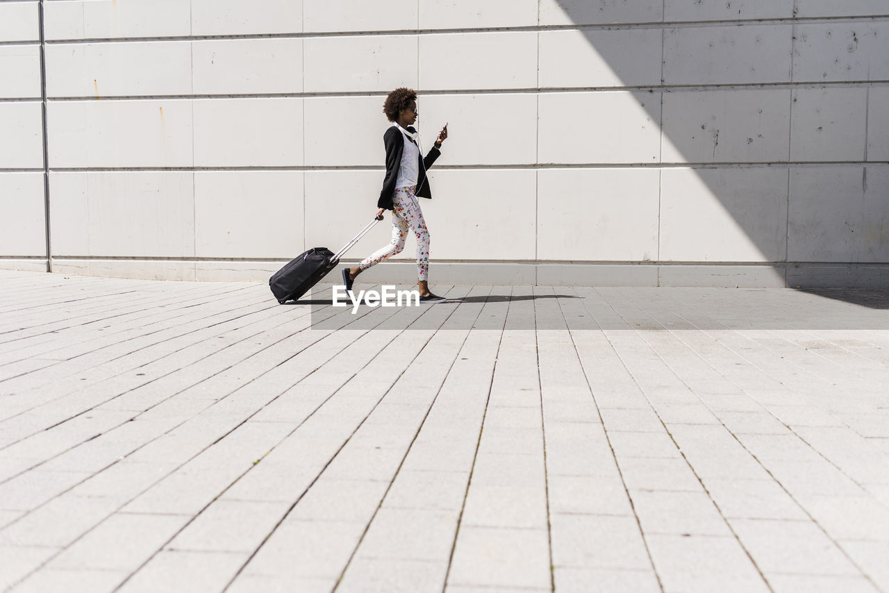 FULL LENGTH OF GIRL WALKING ON FOOTPATH