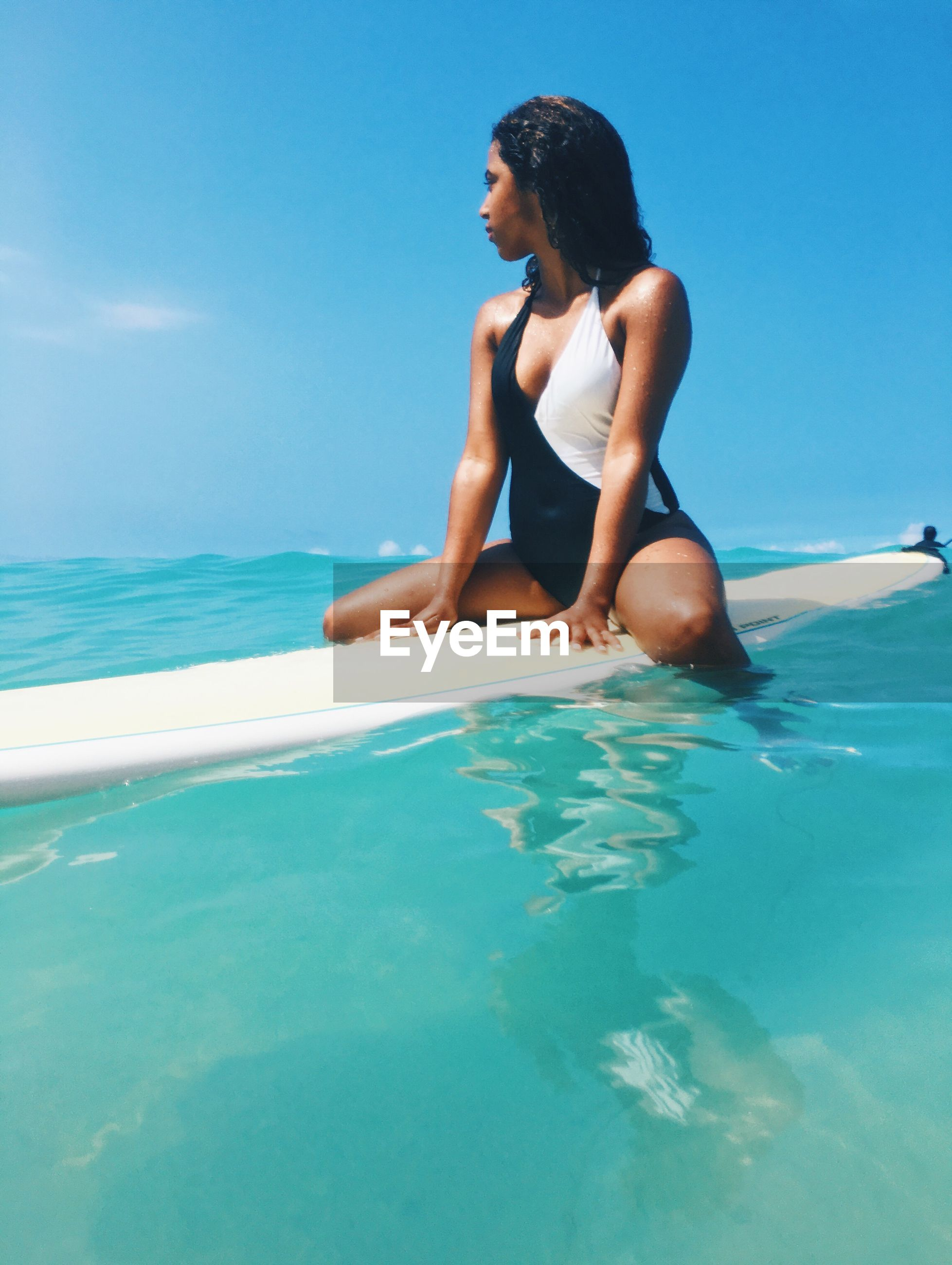Young woman surfing with surfboard on sea against sky