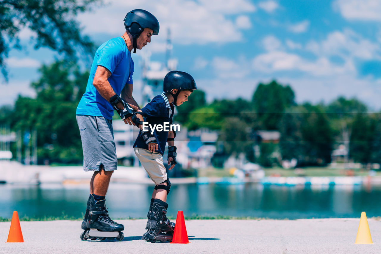 men, child, two people, childhood, helmet, males, day, sport, boys, focus on foreground, real people, full length, headwear, leisure activity, parent, togetherness, people, family, lifestyles, father, son, outdoors