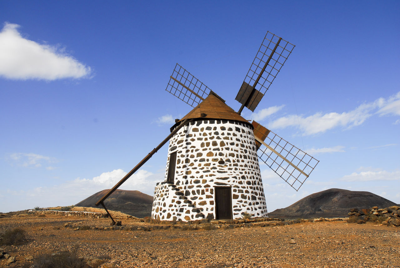 Traditional Windmill On Hill Against Cloudy Sky