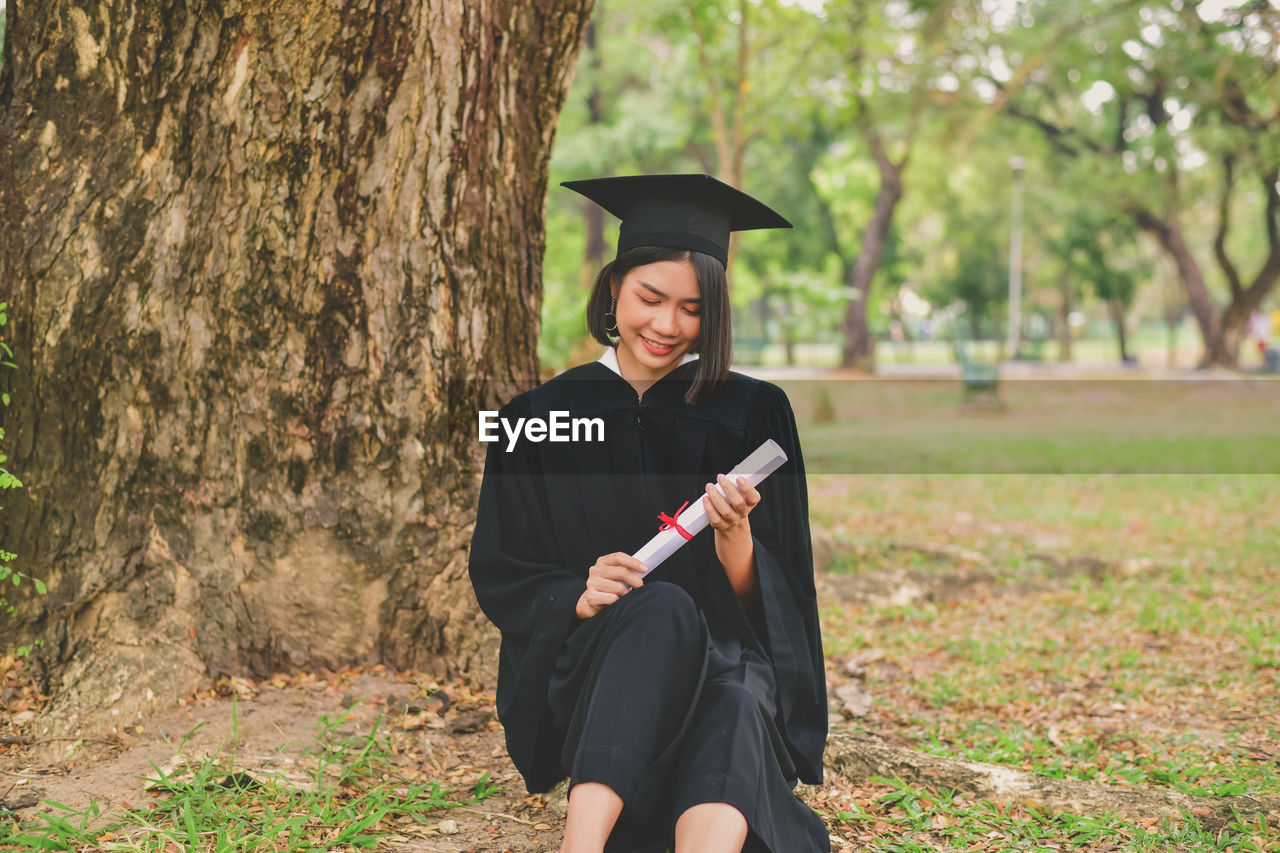 Young Woman In Graduation Gown Sitting On Field At Park