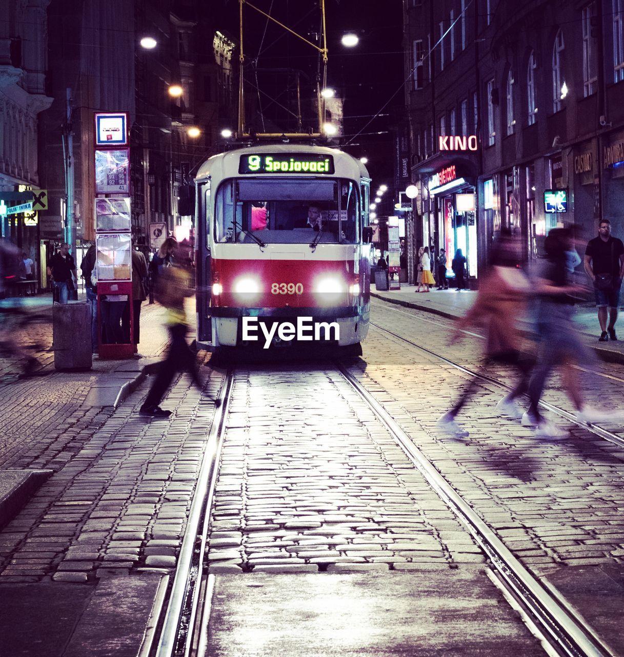 CARS MOVING ON ILLUMINATED STREET AT NIGHT