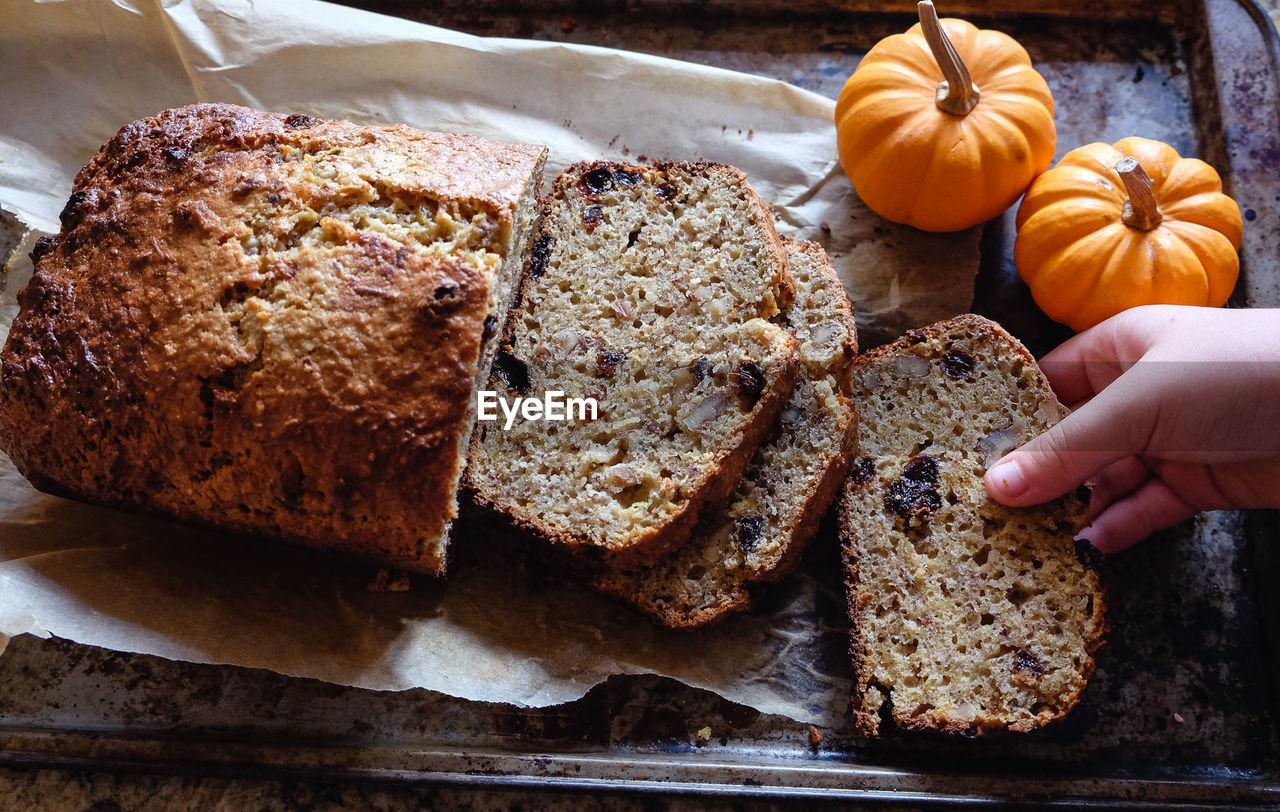 Cropped hand having bread on table