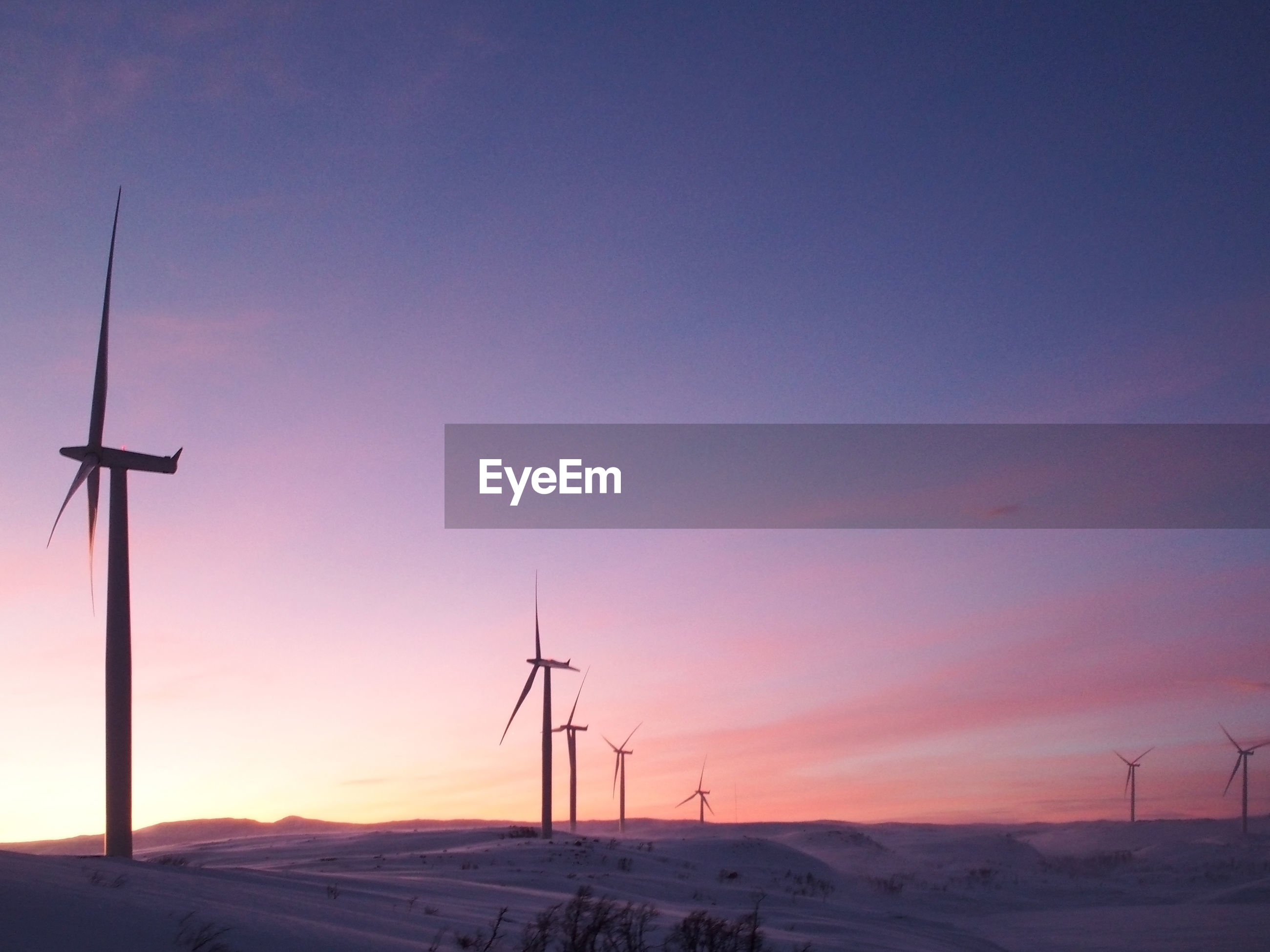 Windmills on snow covered field against sky during sunset