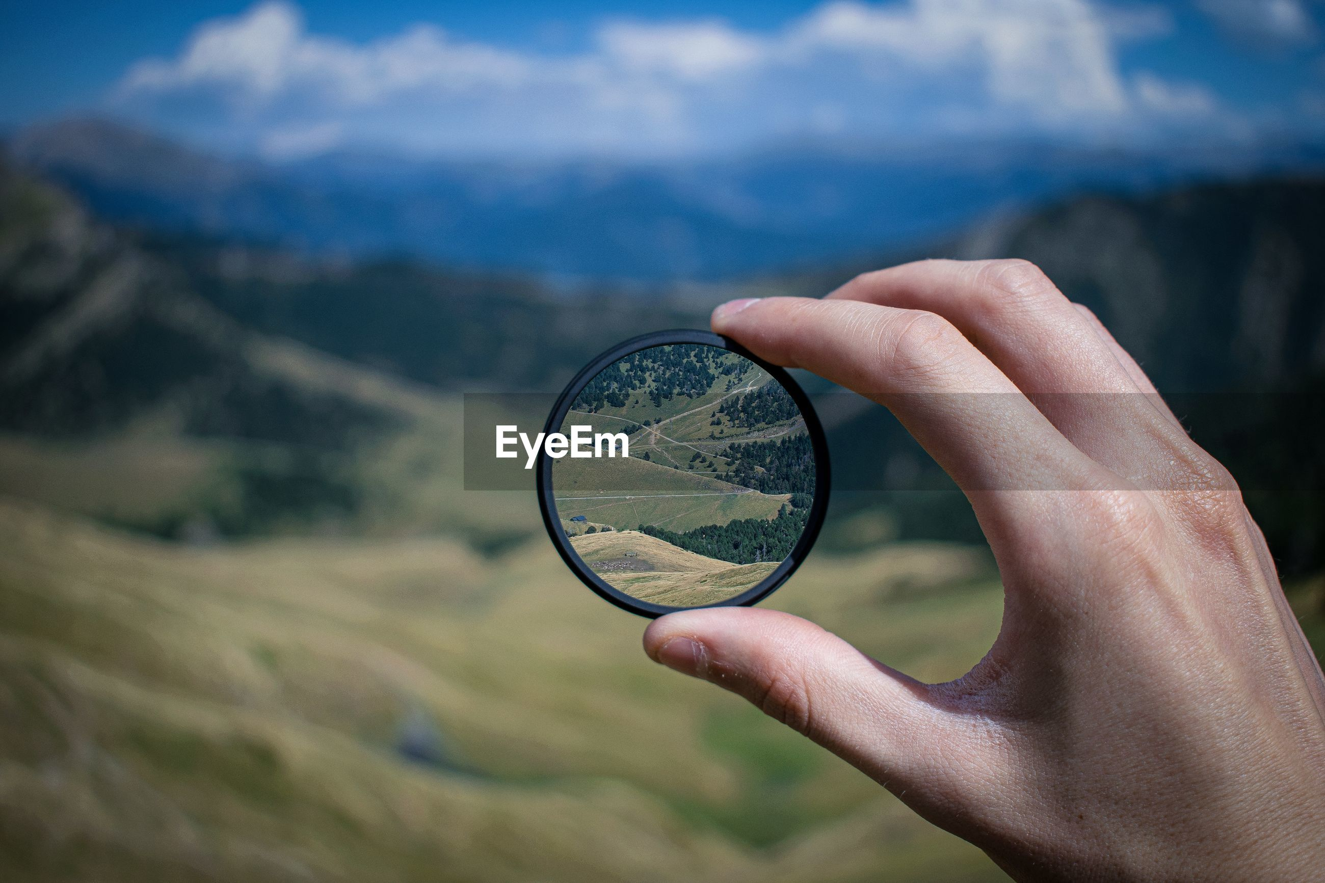 CLOSE-UP OF HAND HOLDING EYEGLASSES AGAINST MOUNTAINS