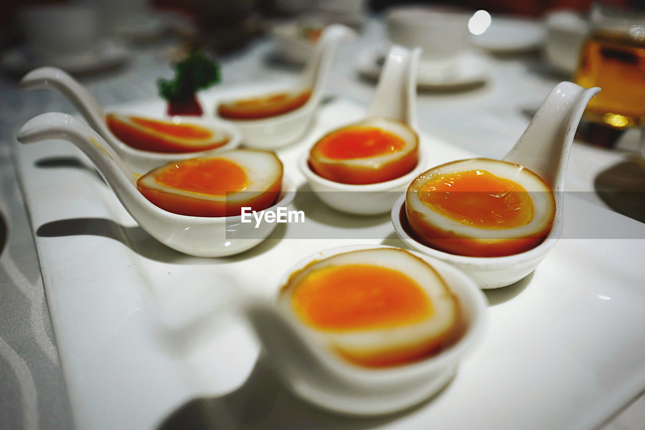 food and drink, indoors, close-up, no people, food, egg, still life, healthy eating, freshness, selective focus, table, high angle view, egg yolk, ready-to-eat, wellbeing, orange color, in a row, serving size, focus on foreground, white color, breakfast, tray, temptation
