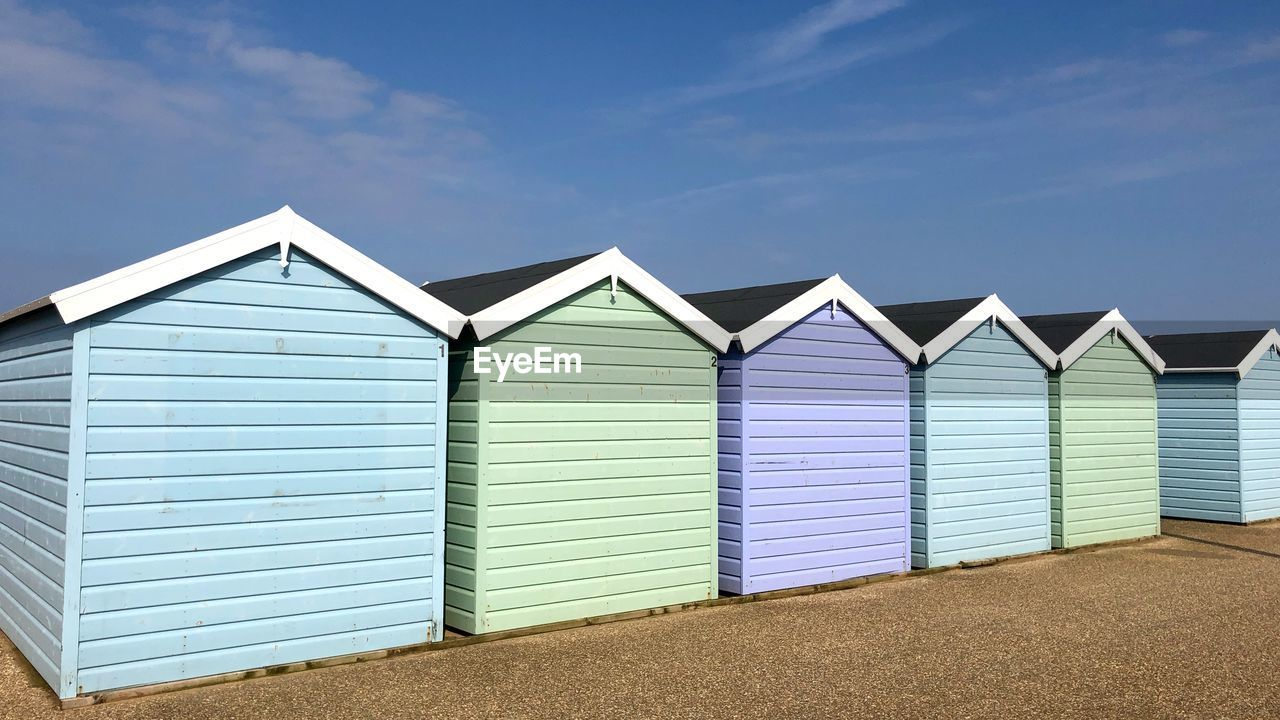 beach hut, sky, hut, built structure, architecture, building exterior, beach, land, side by side, day, in a row, cloud - sky, nature, sand, no people, blue, multi colored, outdoors, building, beauty in nature