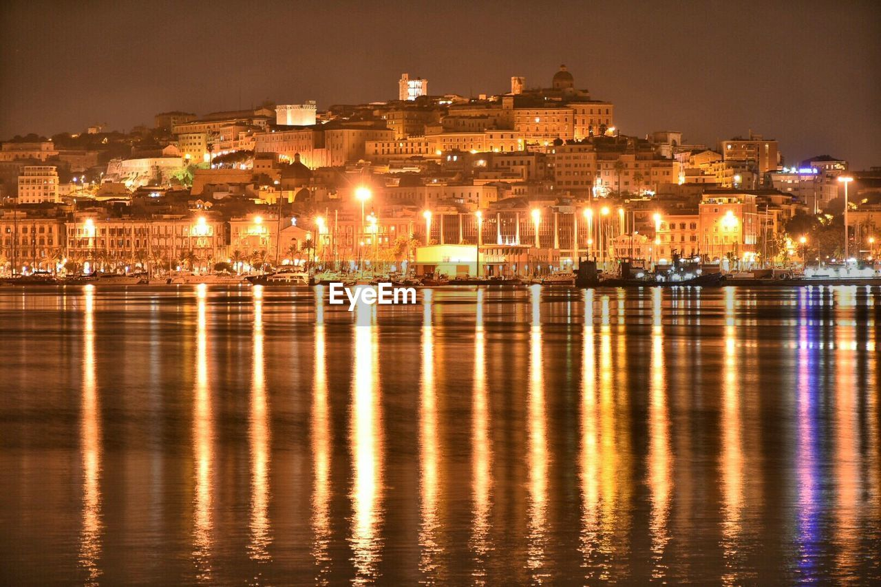 Illuminated Town With Reflection In Sea At Cagliari