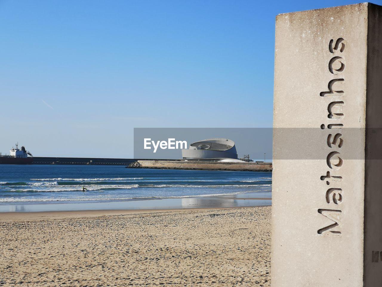 TEXT ON BEACH AGAINST CLEAR BLUE SKY