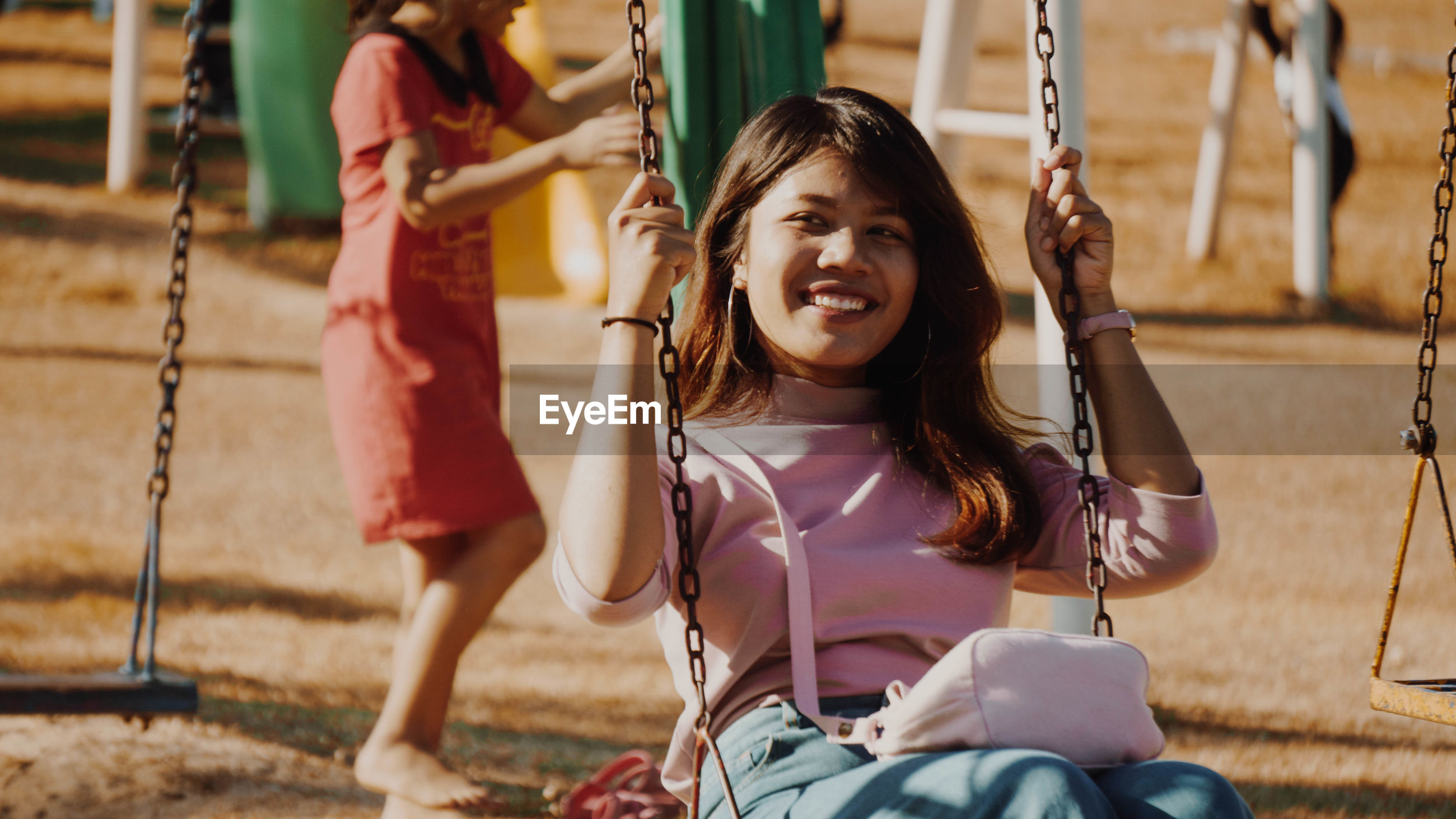Happy young woman looking away while swinging at park