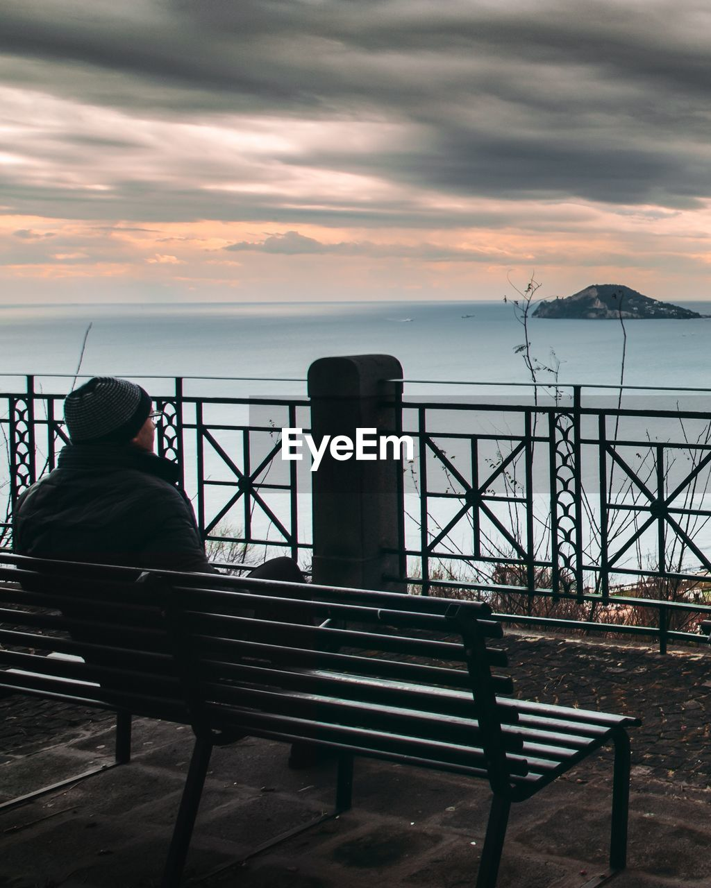 sea, water, railing, nature, real people, scenics, sky, one person, sunset, horizon over water, beauty in nature, tranquil scene, rear view, fishing pole, idyllic, tranquility, cloud - sky, outdoors, leisure activity, fishing, sitting, relaxation, full length, day, lifestyles, men