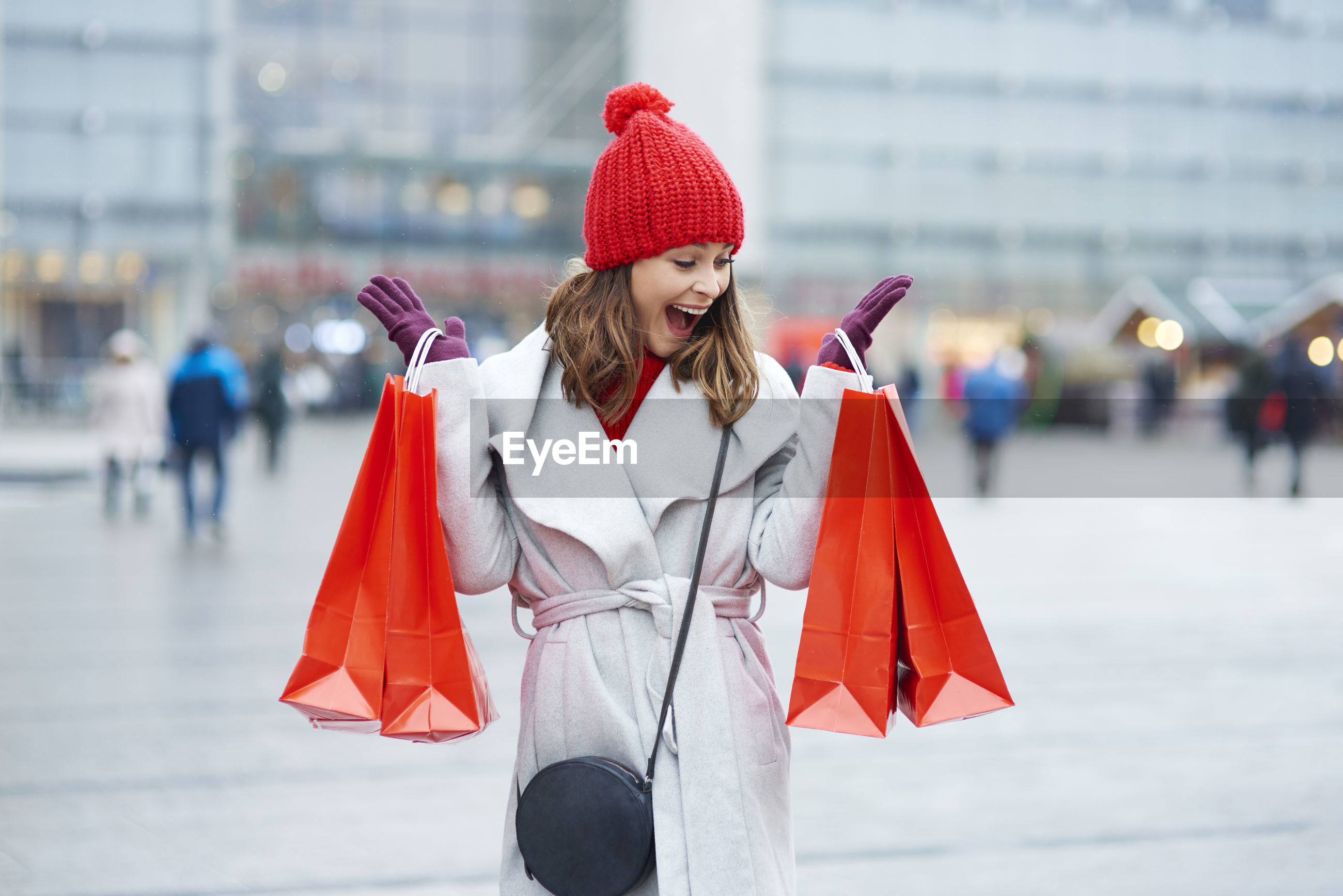 Happy woman holding shopping bags while standing in city during winter
