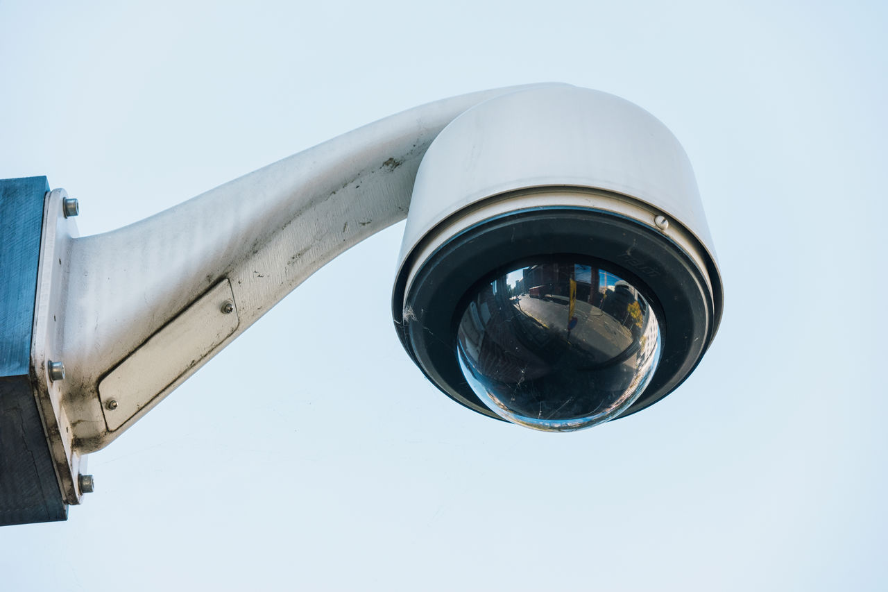 Low Angle View Of Surveillance Camera Against White Background