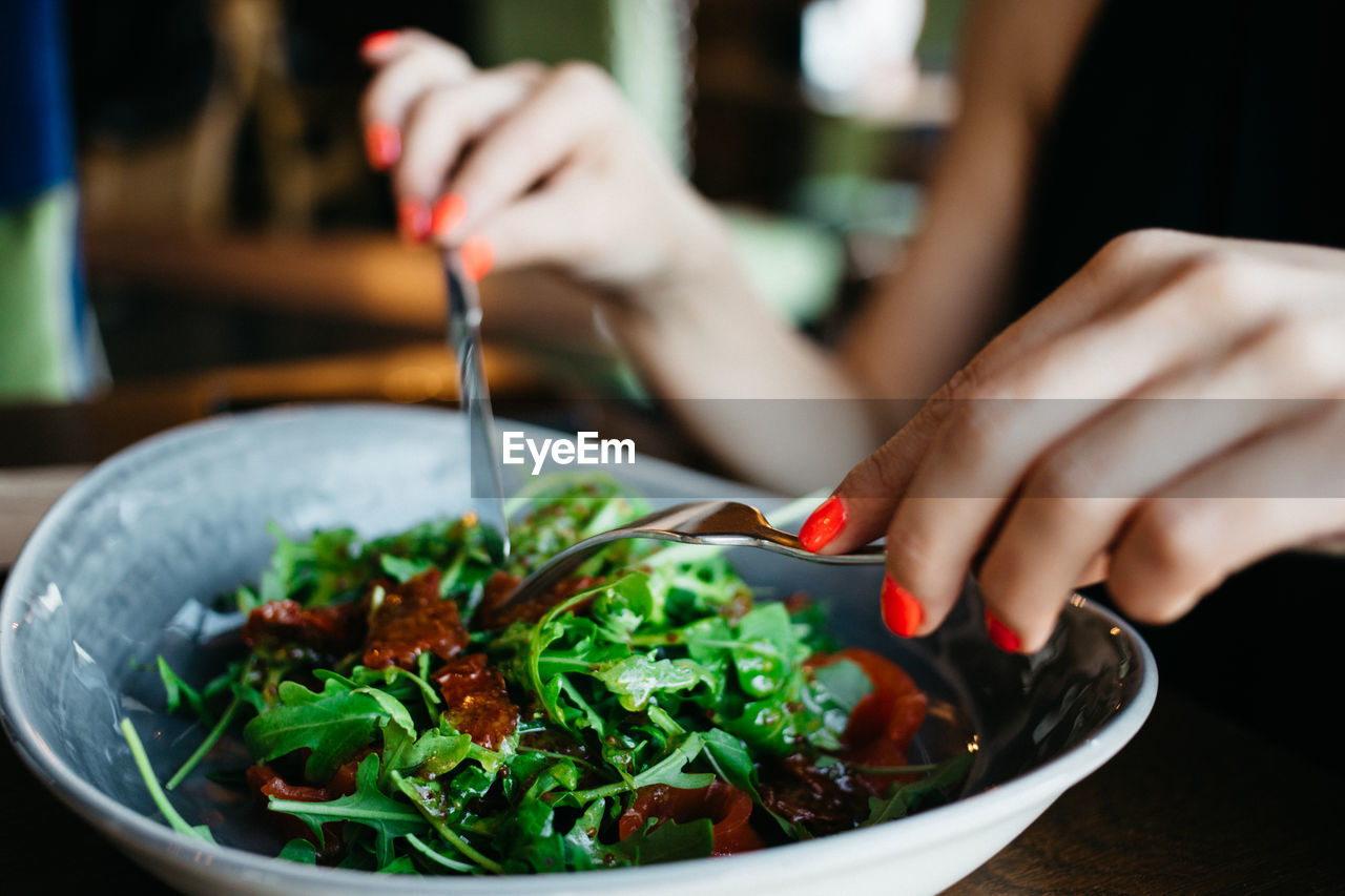 Cropped Image Of Woman Having Salad From Bowl In Restaurant