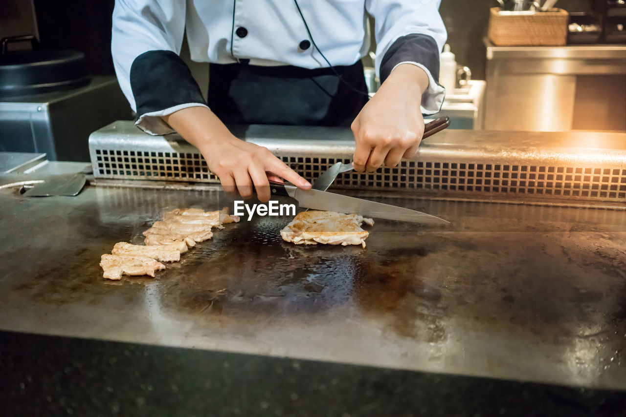food and drink, food, one person, preparation, midsection, preparing food, chef, kitchen, freshness, indoors, commercial kitchen, occupation, real people, front view, holding, food and drink establishment, business, hand, human hand, working, skill, uniform, japanese food