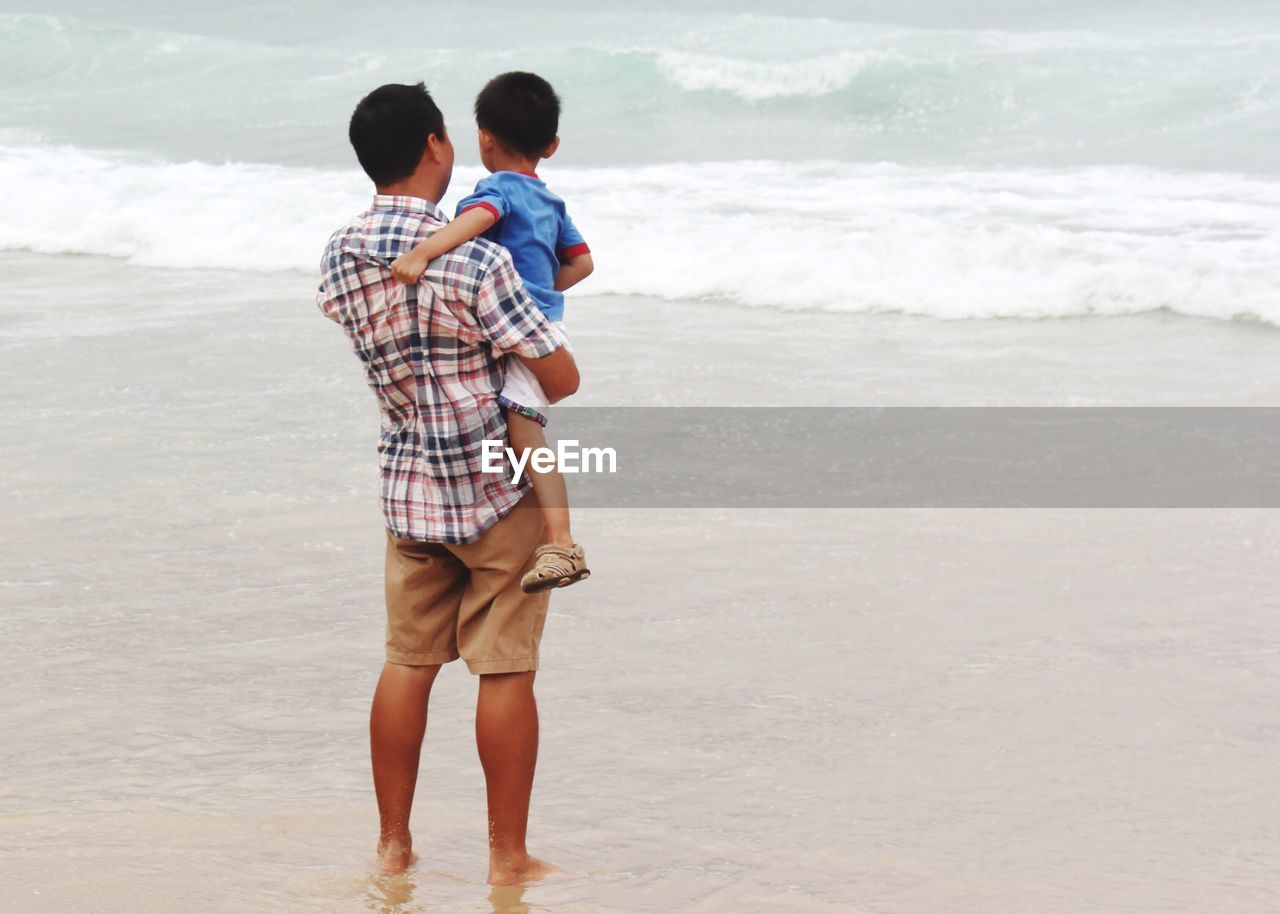 Rear View Of Father Carrying Son At Beach