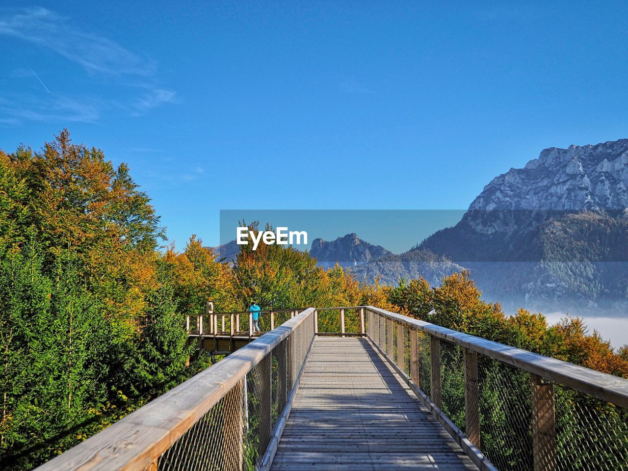 mountain, sky, direction, the way forward, railing, beauty in nature, plant, scenics - nature, nature, tree, wood - material, tranquility, blue, tranquil scene, day, footpath, no people, connection, outdoors, architecture, footbridge, wood paneling