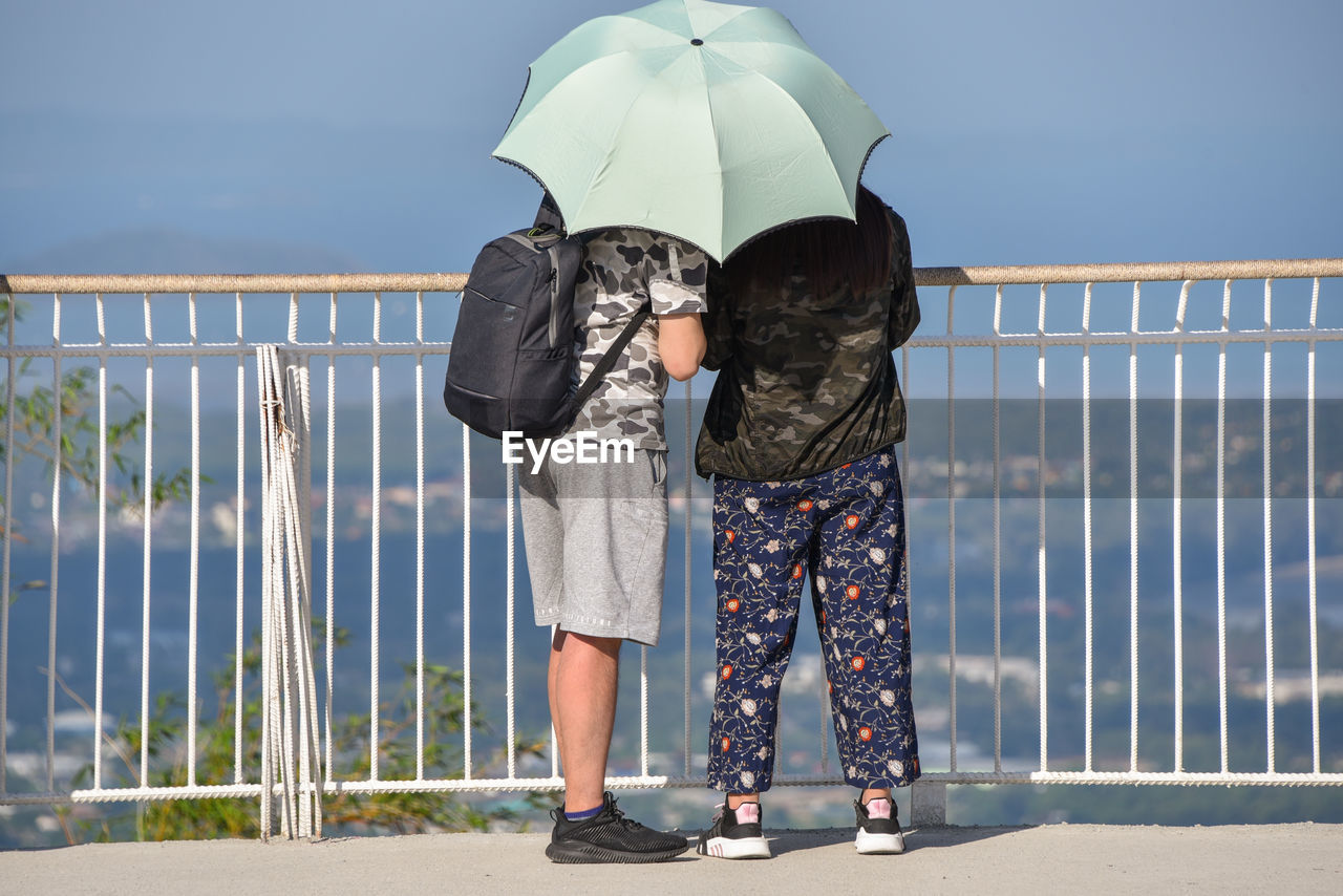 real people, railing, rear view, nature, lifestyles, sky, standing, full length, women, water, people, casual clothing, day, protection, leisure activity, sunlight, adult, security, outdoors, shorts