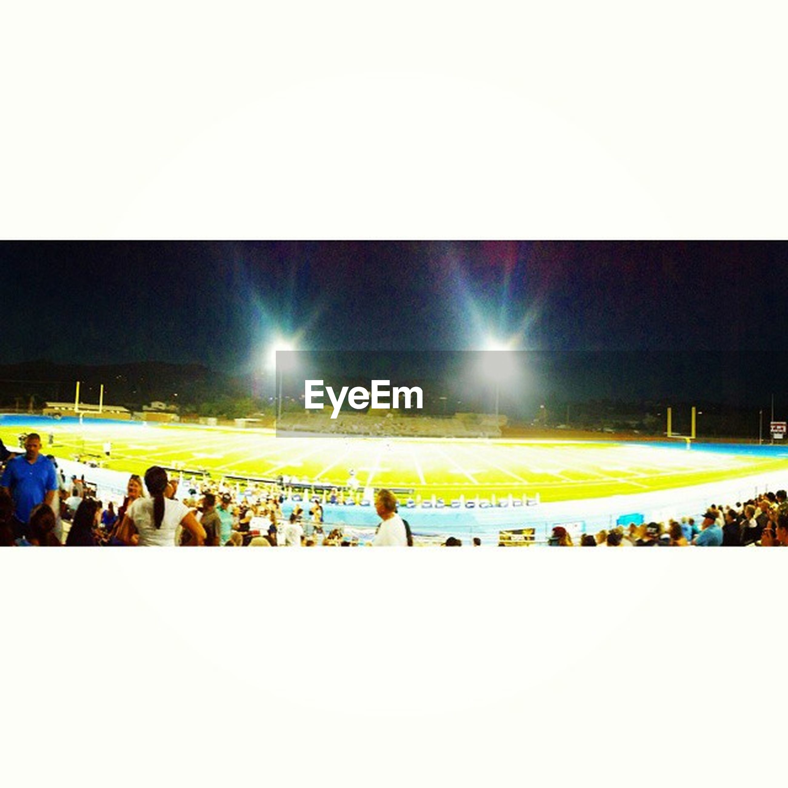 large group of people, lifestyles, leisure activity, men, person, enjoyment, crowd, illuminated, togetherness, fun, night, arts culture and entertainment, copy space, standing, clear sky, mixed age range, stadium, auto post production filter