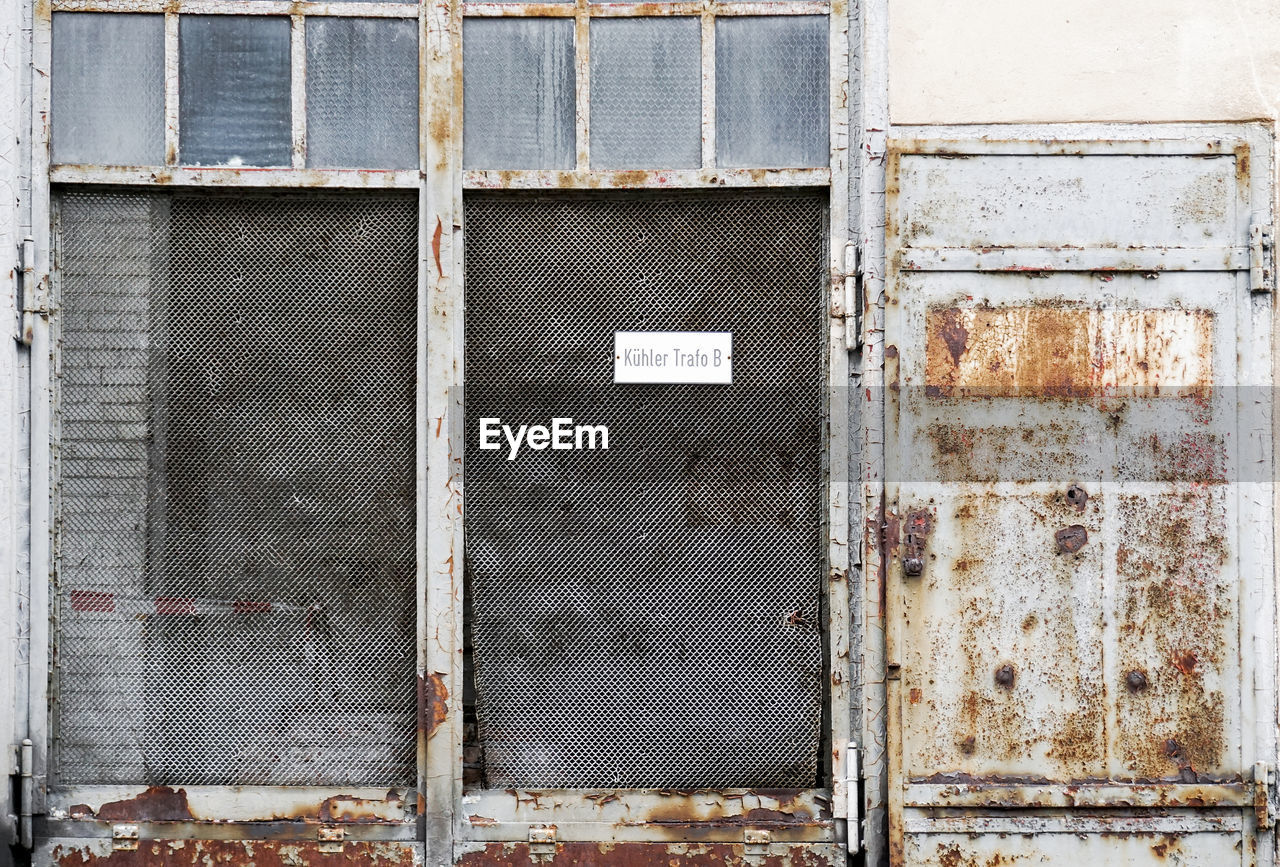 built structure, architecture, building exterior, no people, wall - building feature, metal, door, old, closed, entrance, security, safety, day, protection, weathered, rusty, outdoors, pattern, backgrounds, run-down, deterioration, iron