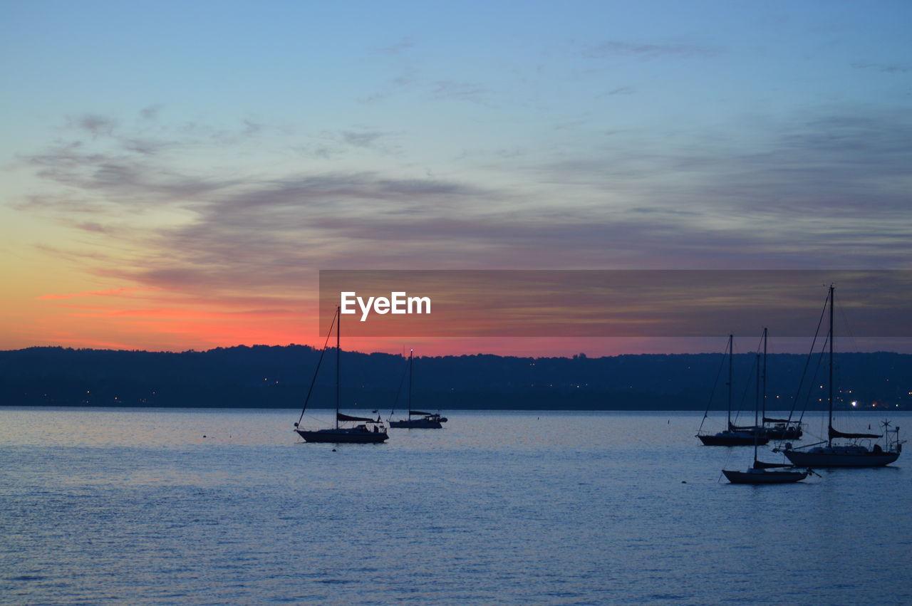 Boats sailing in hudson river against orange sky