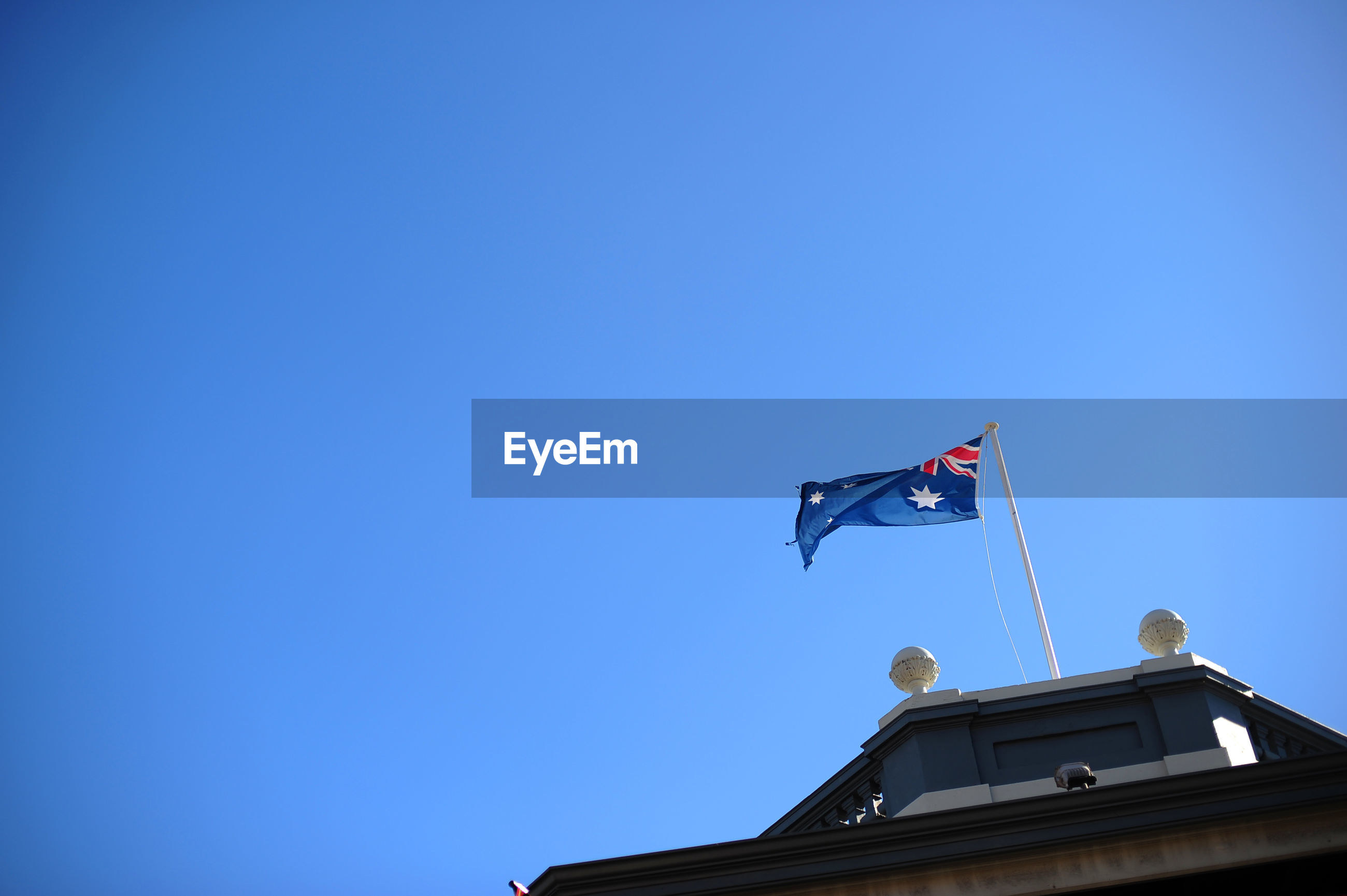 Low angle view of flag on building against clear blue sky