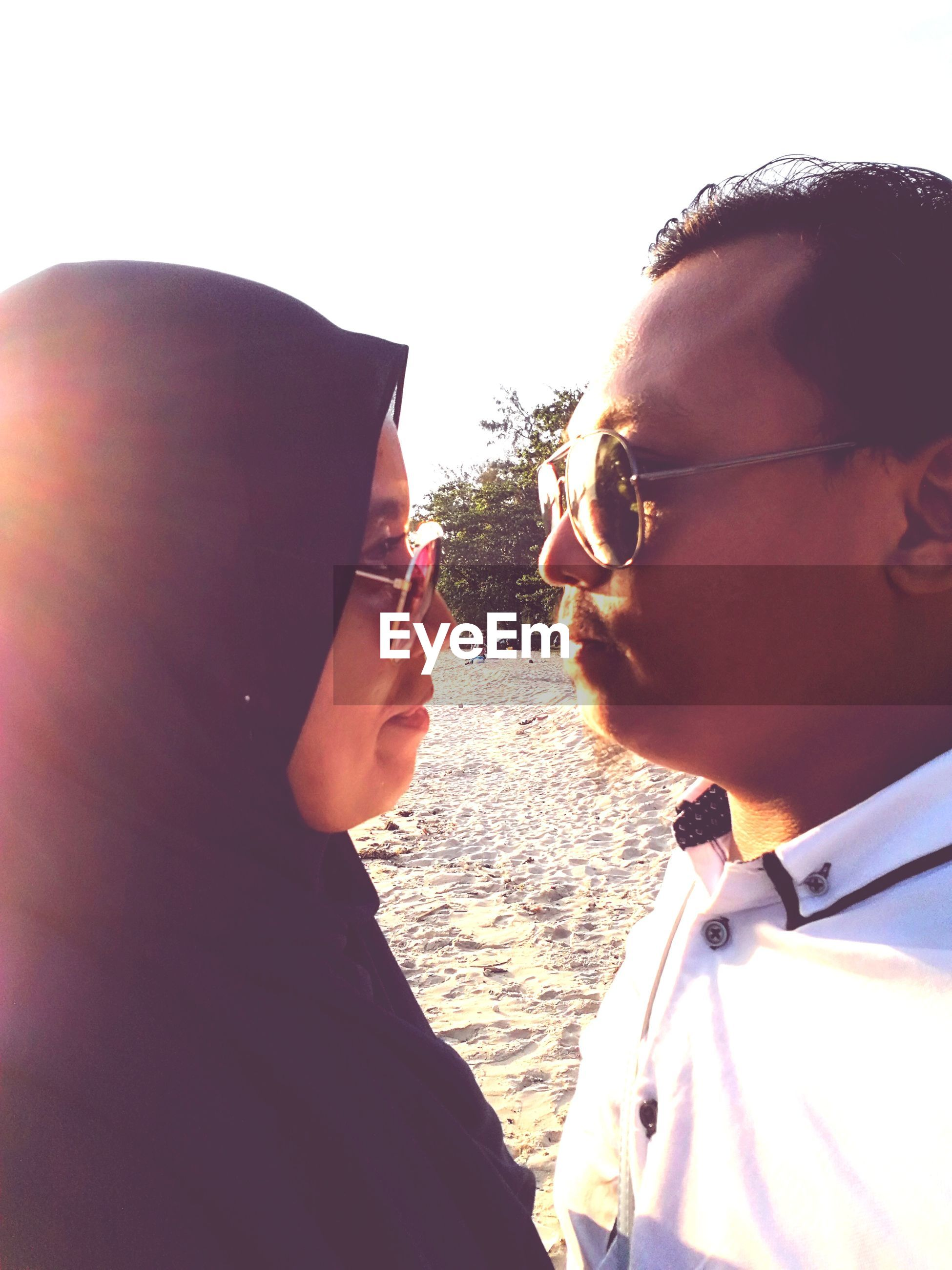 Close-up of couple at beach against sky