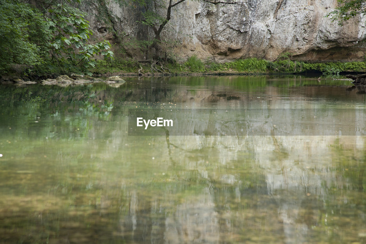 reflection, water, lake, no people, nature, day, waterfront, plant, outdoors, rock, green color, backgrounds, tranquility, tree, solid, textured, forest, land, rock - object, textured effect