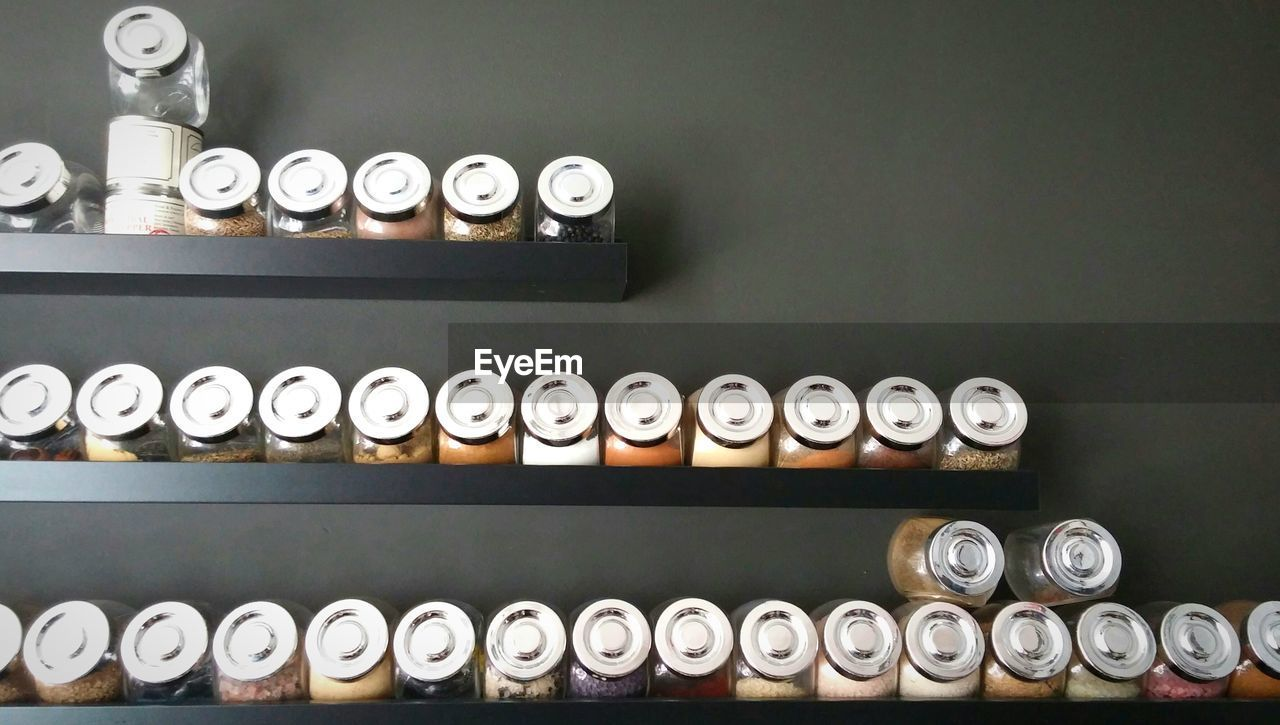 Jars Of Spices Arranged On Shelves At Home